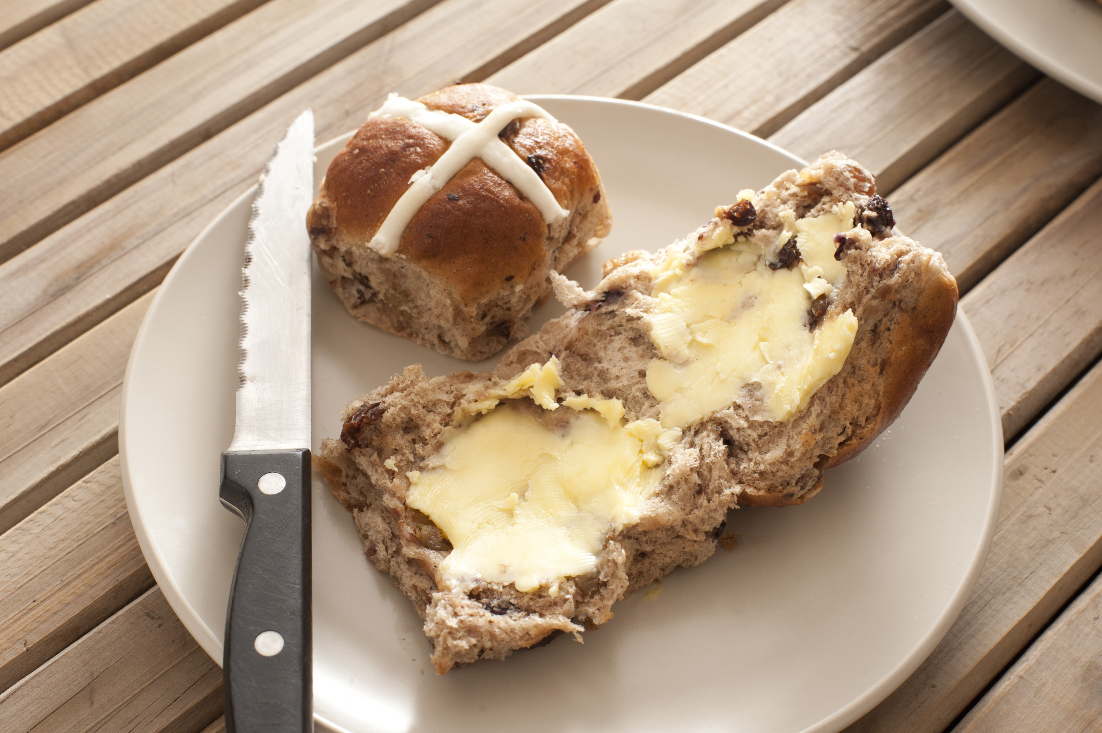 Photo of bread with butter, bun and knife on plate on wooden table. Daylight