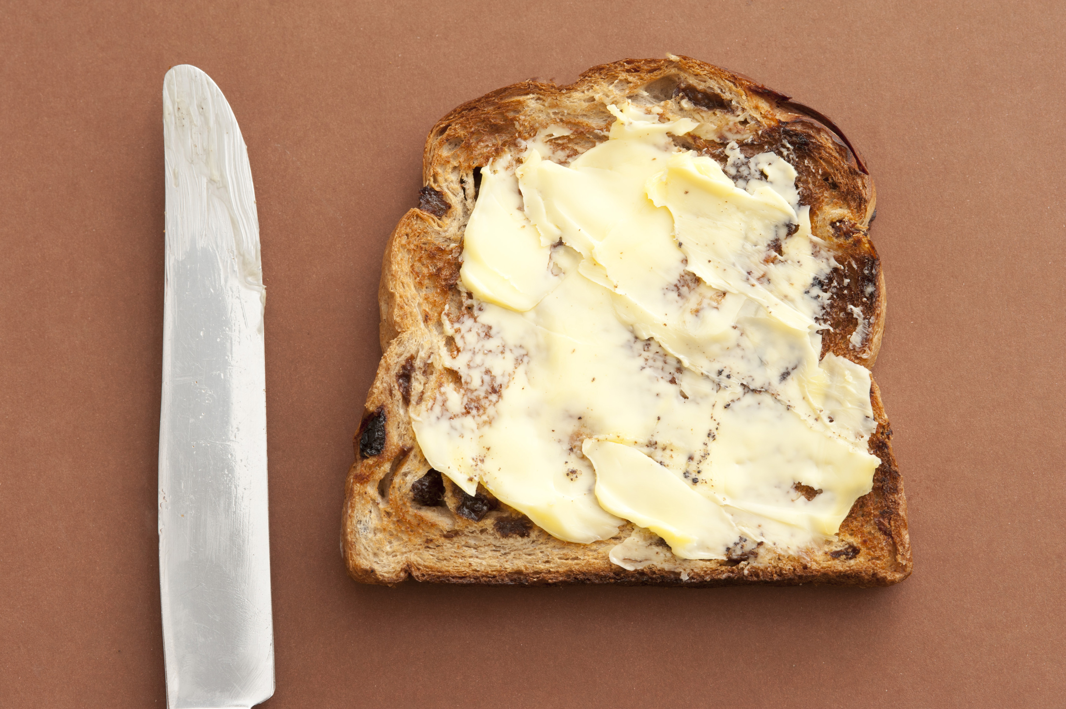 Close-up of delicious slice of bread with spreading butter and knife on brown background. From above