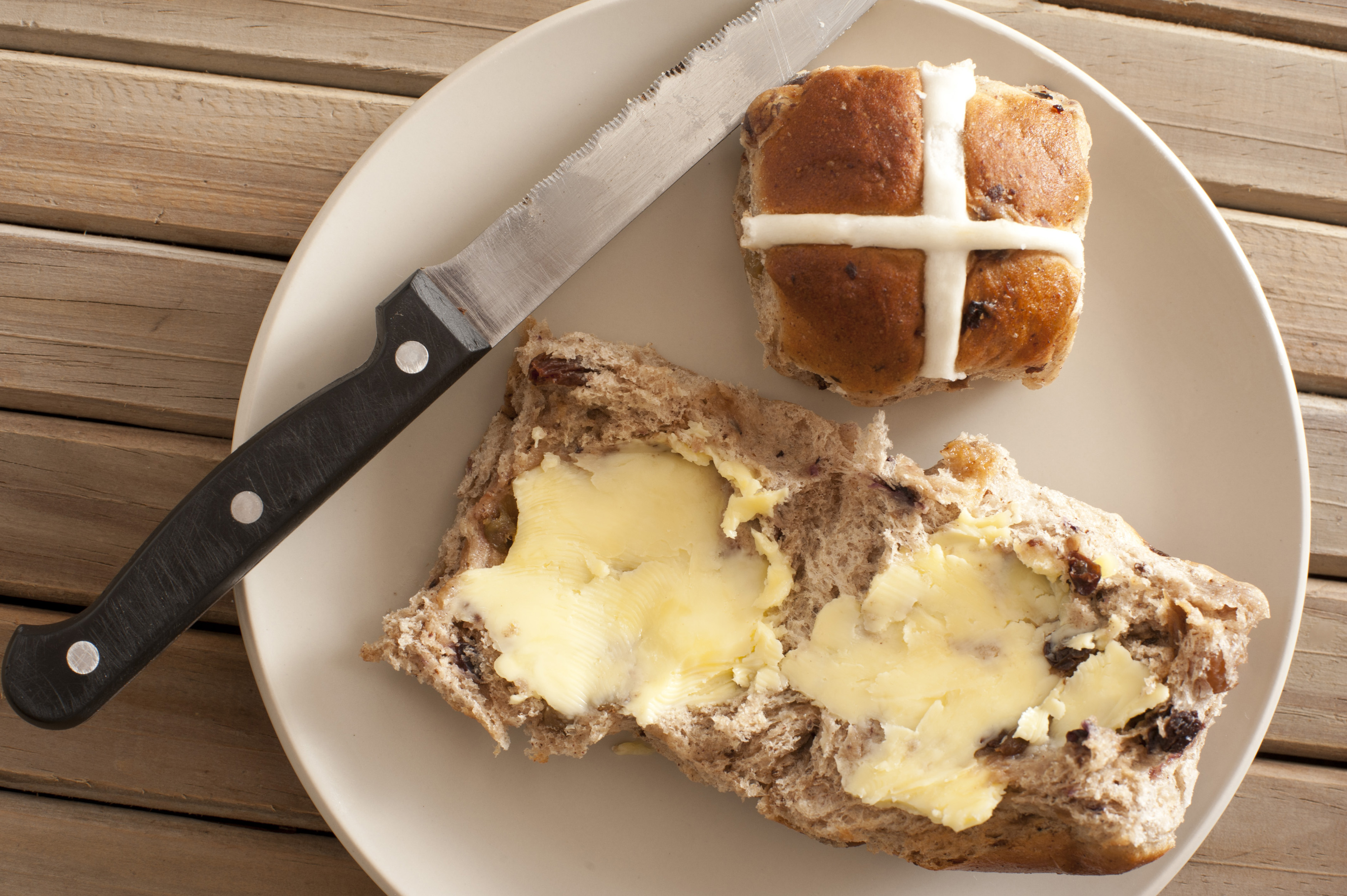 Fresh buttered spicy traditional hot cross bun to celebrate Easter with a whole one alongside to display the cross, overhead view on a plate with a knife