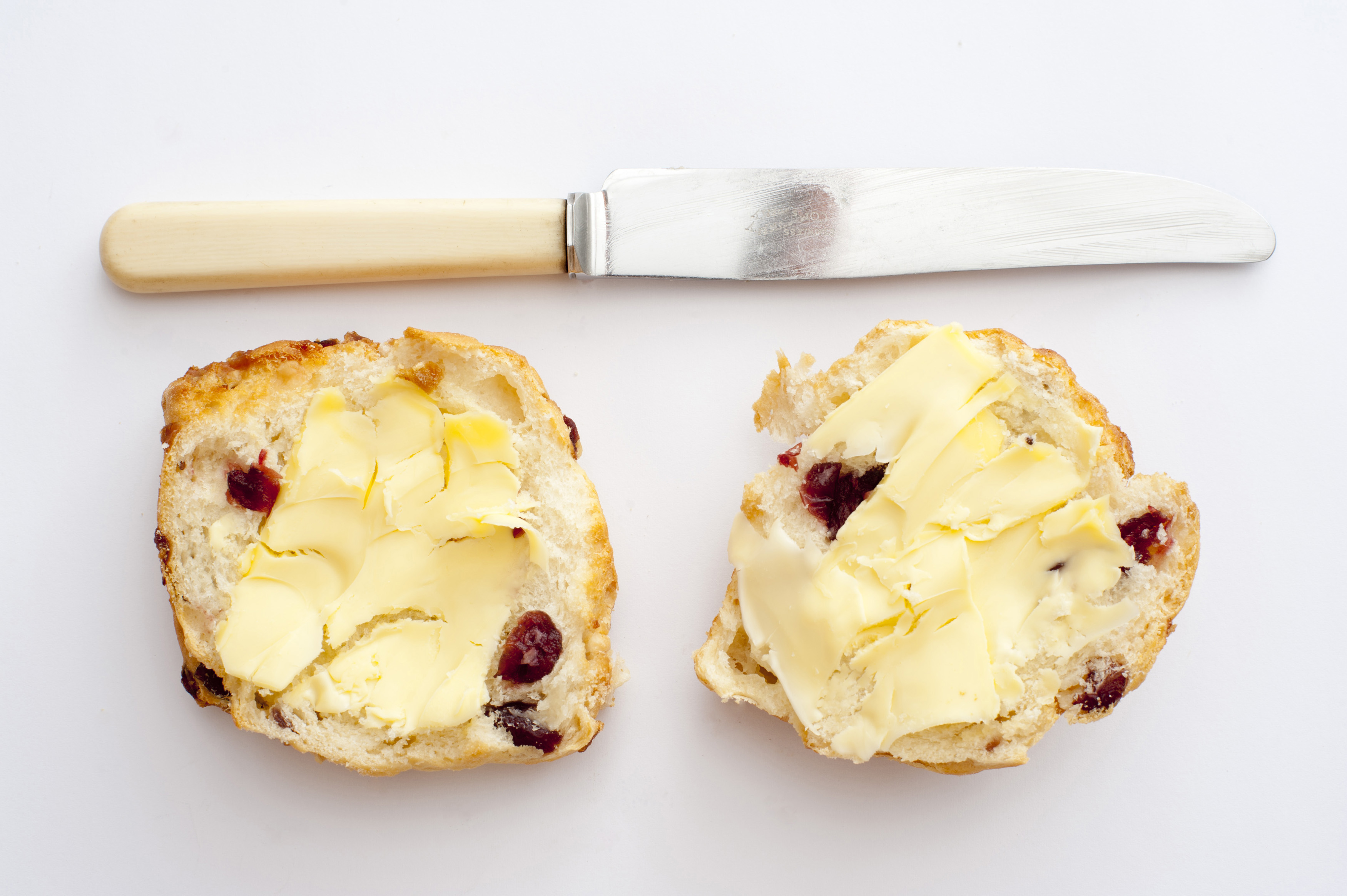 Still life of two sandwiches with butter and dried berries, knife. Isolated, from above