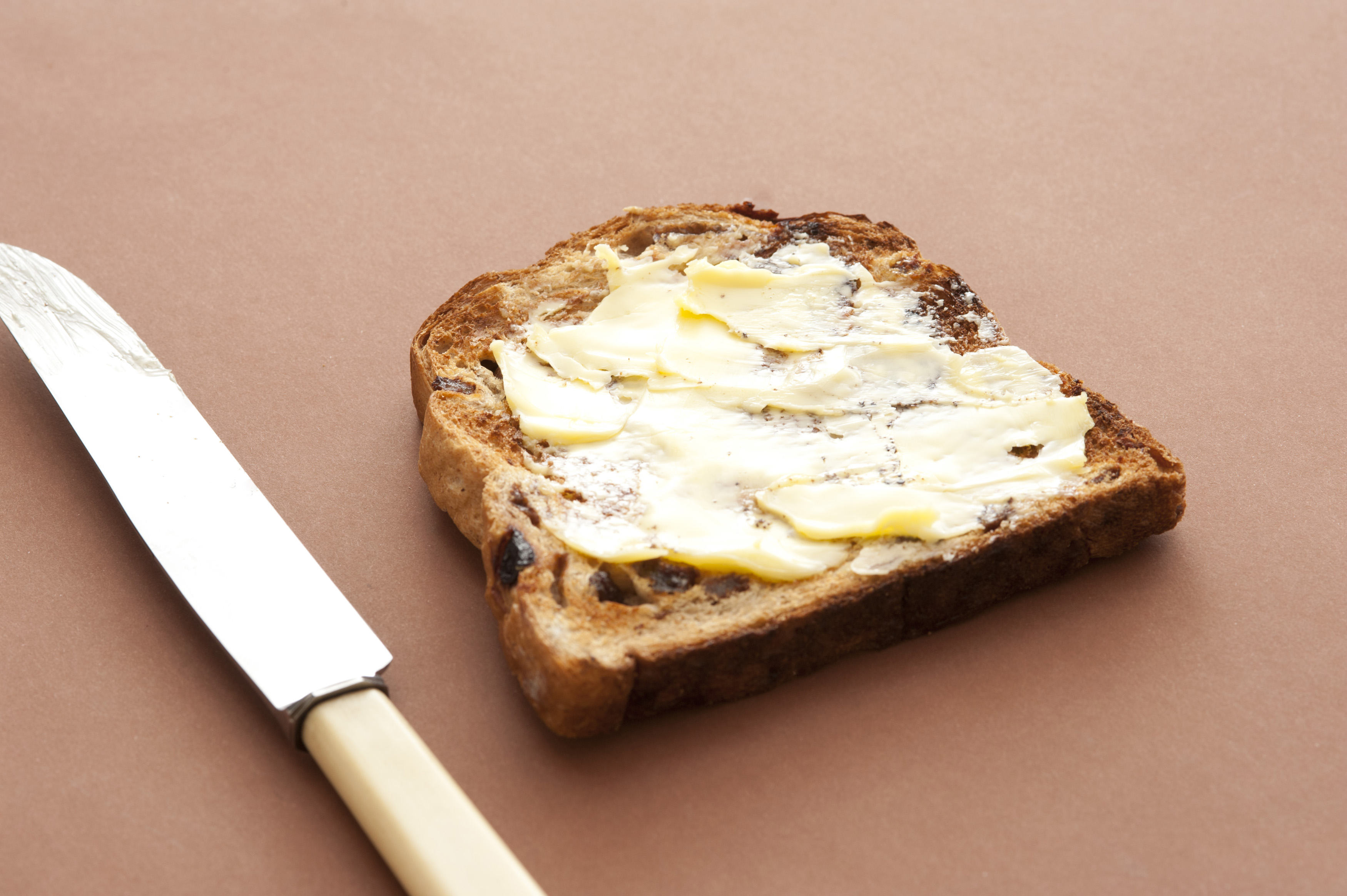 Buttered toasted bread with a thick spread of butter on a slice of fruity raisin bread on a brown background with a knife