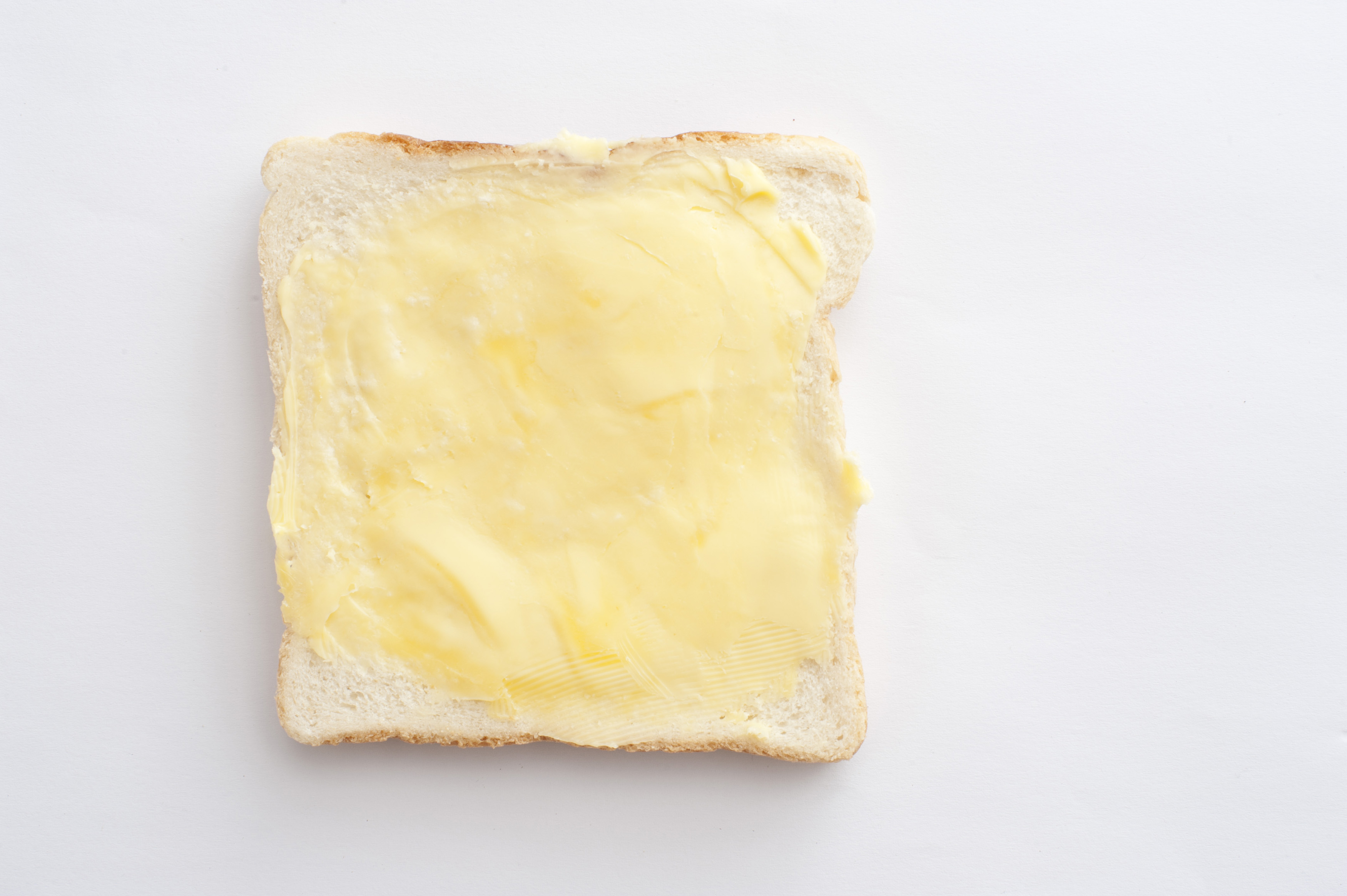 Single slice of buttered white bread ready to make a snack or sandwich on a white background with copyspace, overhead view
