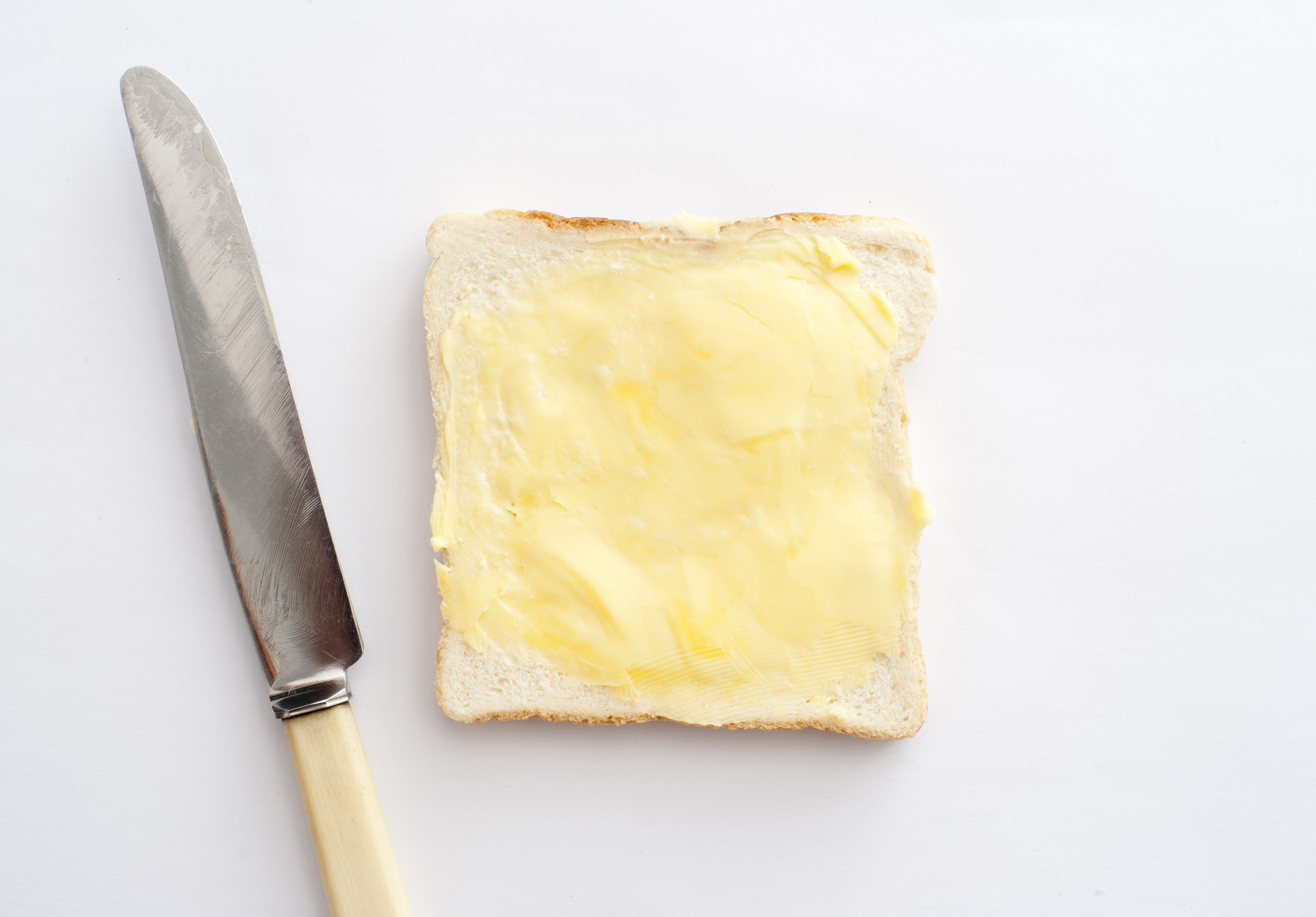 Isolated slice of white bread with butter and knife on white background. From above
