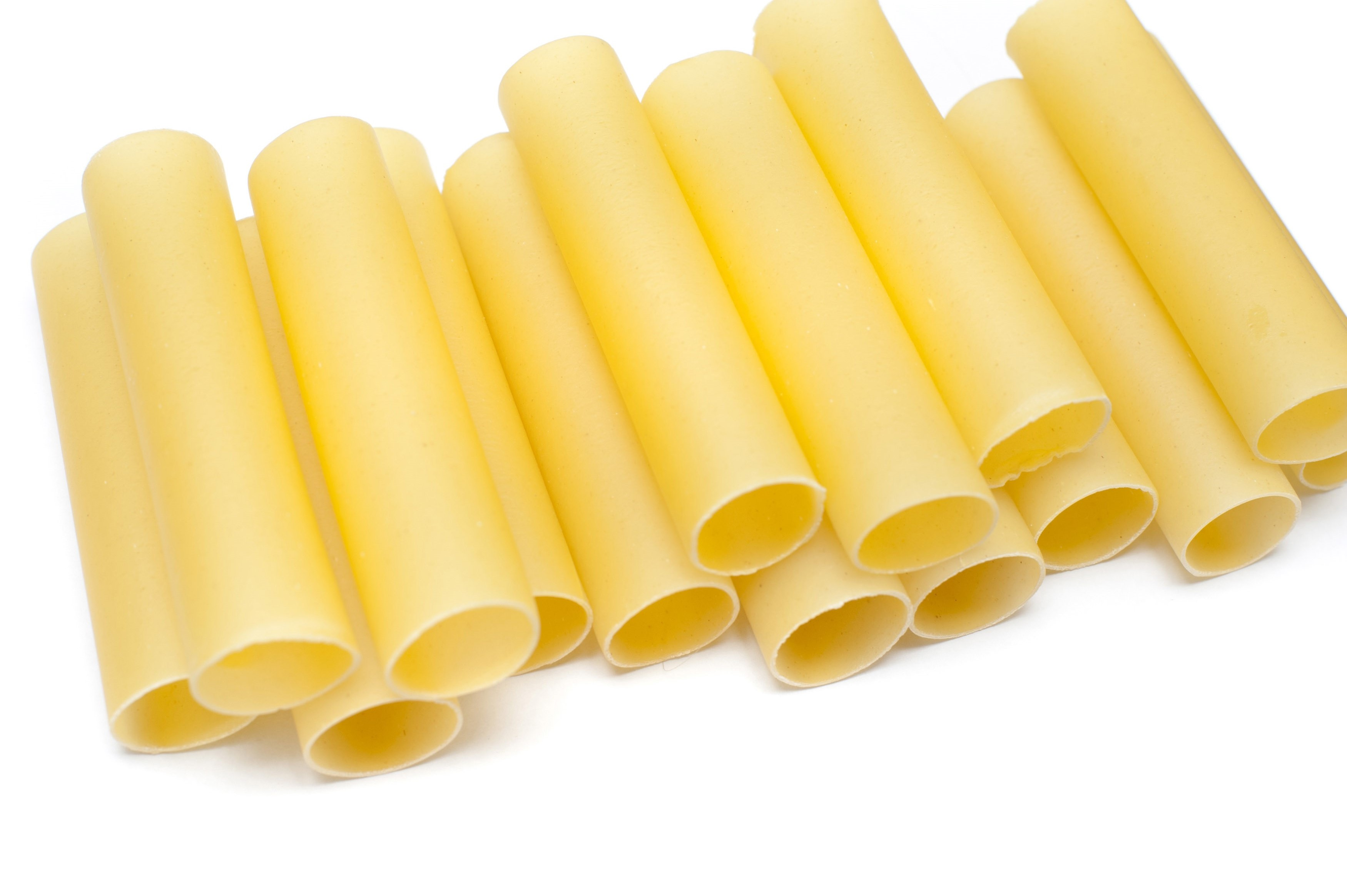 Close up of a stack of dried cannelloni pasta, a tubular pasta that is stuffed with meat or vegetables, on a white background