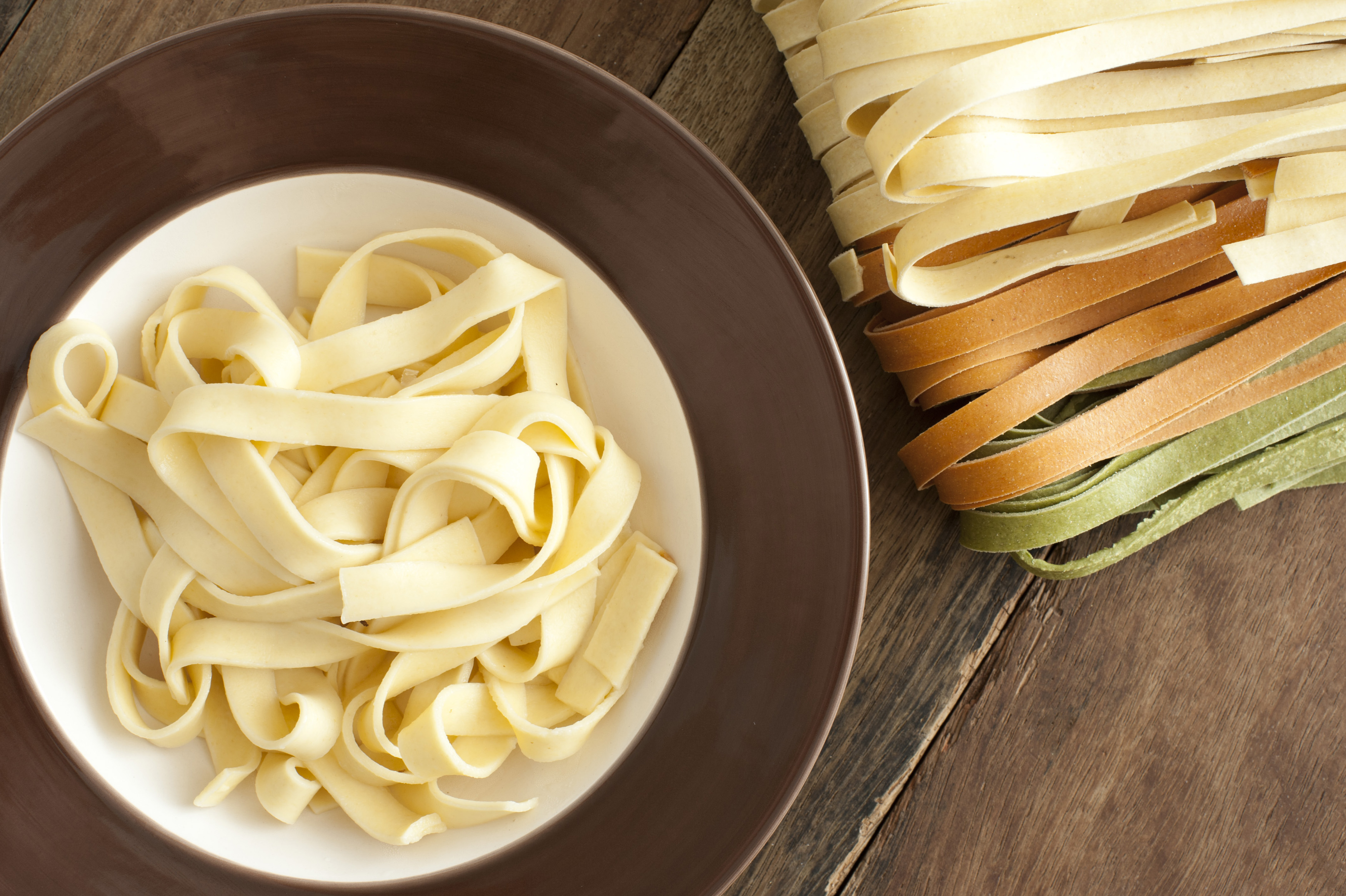 Cooked and dried Italian tagliatelle pasta viewed from above with a serving of plain boiled pasta in a bowl alongside white, brown and green dried ribbons on a wooden table