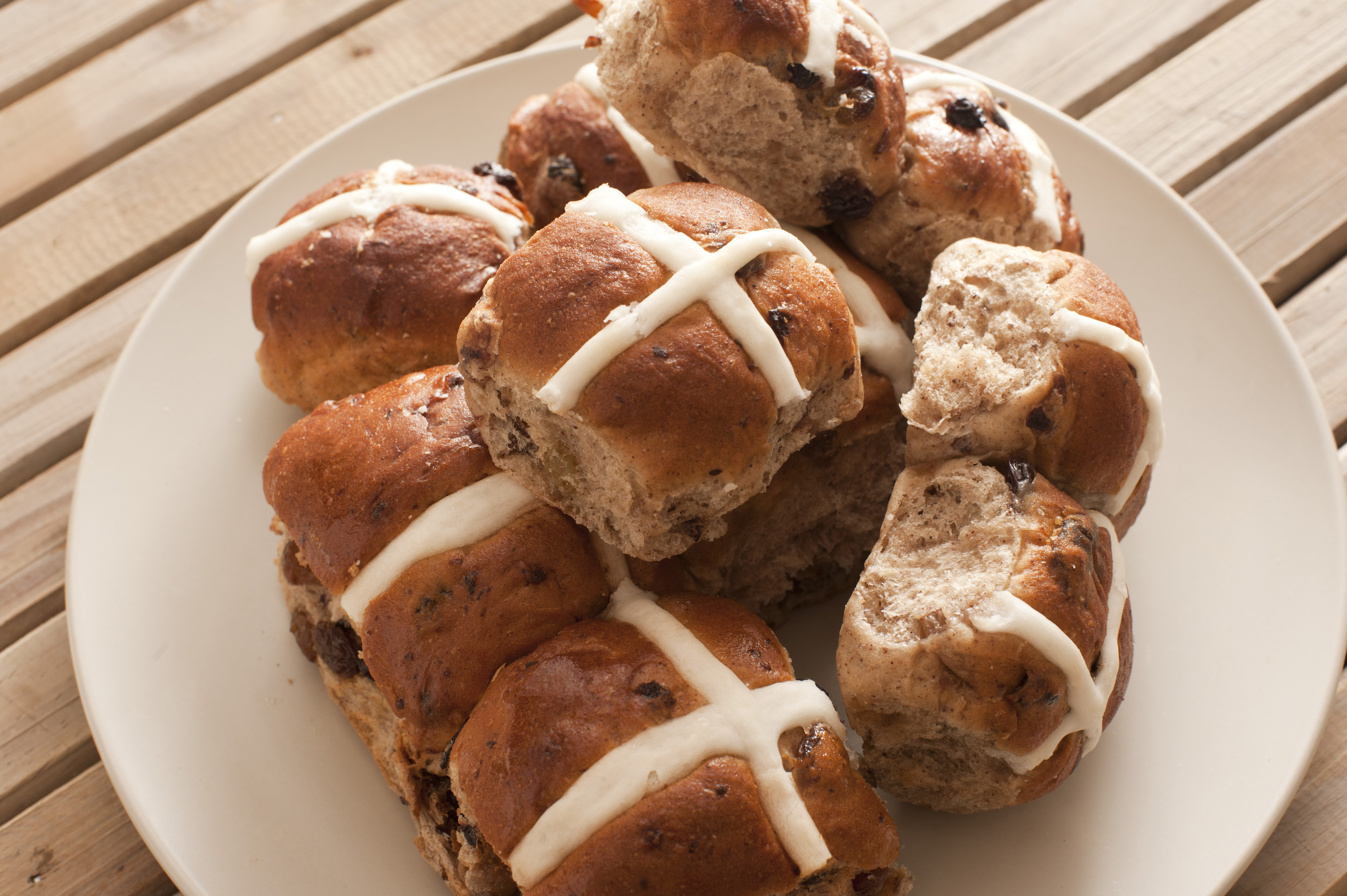 Batch of delicious spicy hot cross buns with raisins served on a plate for an Easter snack symbolising the crucifixion of Christ
