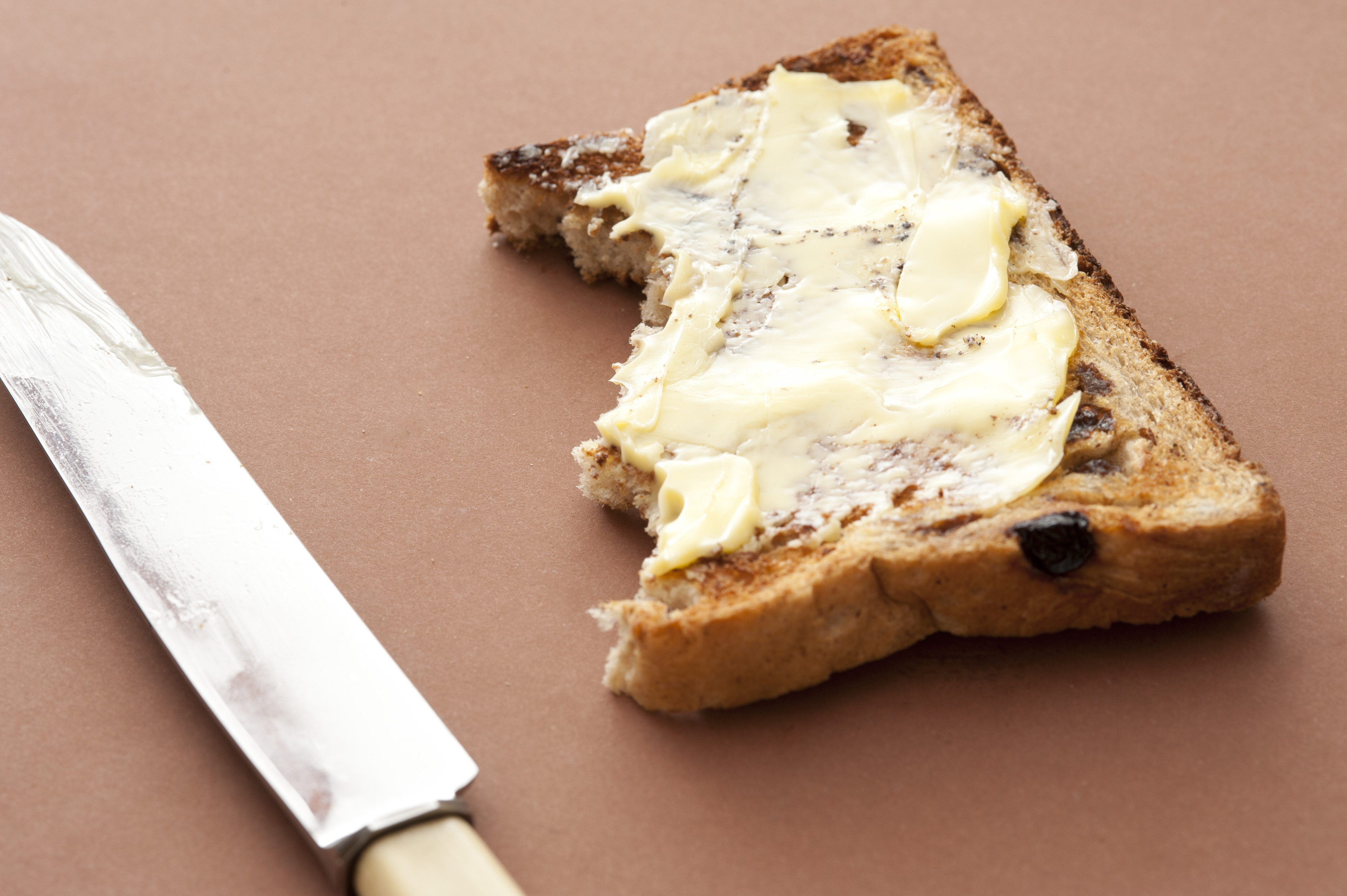 Half eaten slice of buttered raisin bread with bite marks on a brown background alongside a knife