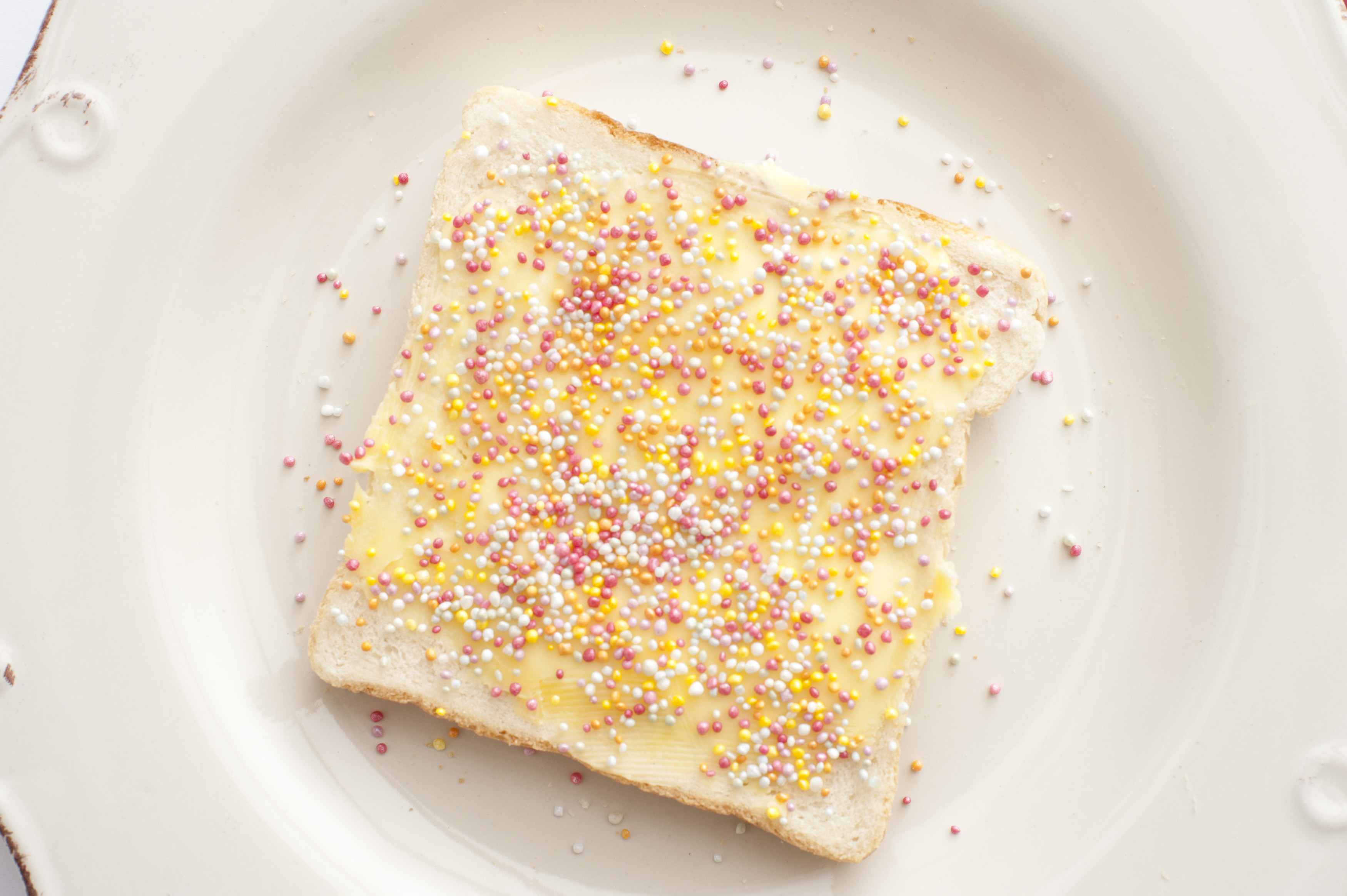 Buttered slice of white fairy bread covered in colorful sprinkles for a childhood treat for kids, overhead view on a white plate