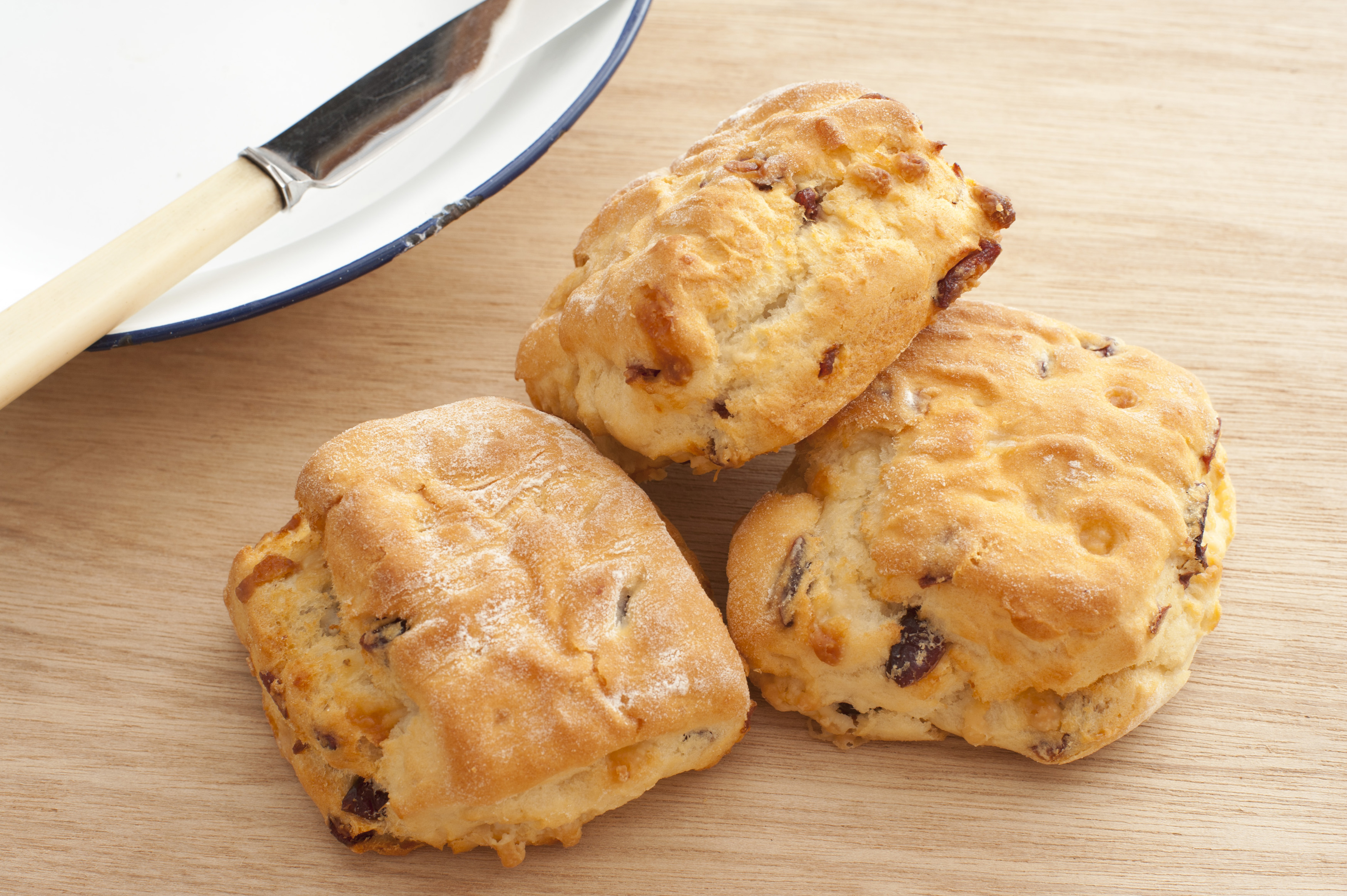Three freshly baked delicious homemade scones with raisins on a wooden kitchen counter alongside a plate and knife