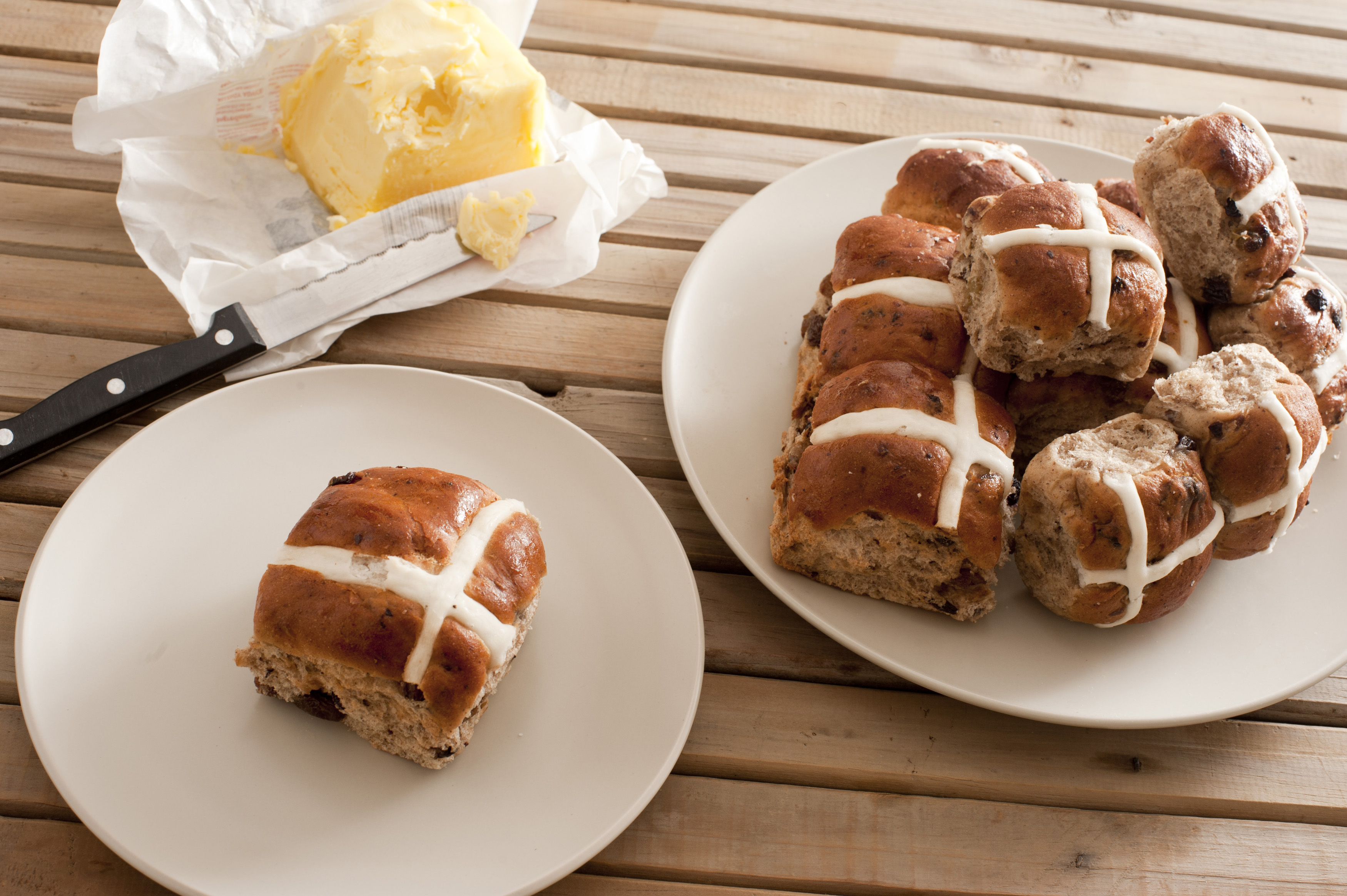 Batch of freshly baked hot cross buns with a single bun on a plate and pat of farm butter, high angle view