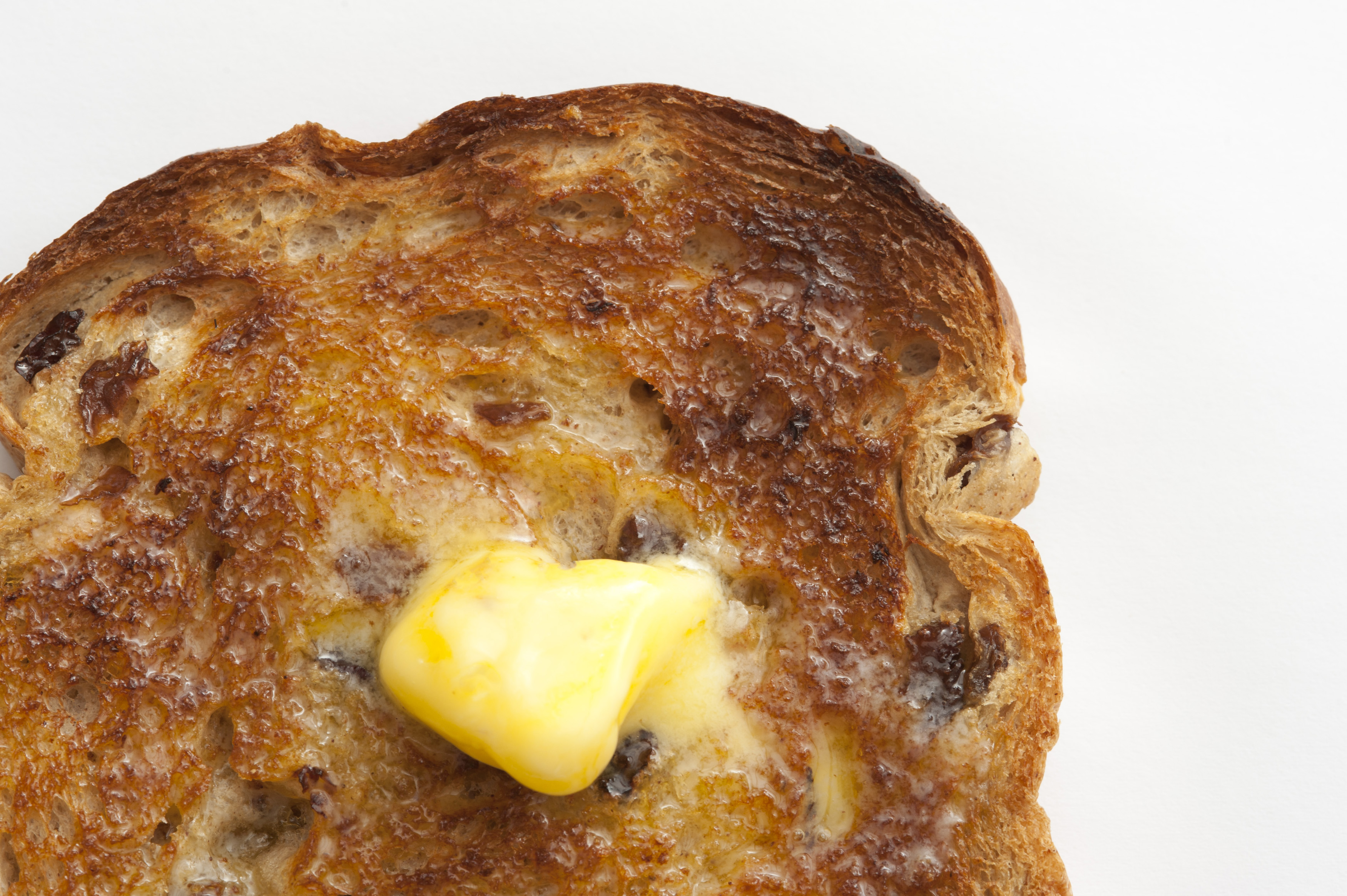 Dollop of melted fresh farm butter on a hot slice of toast with raisins viewed close up from above over white