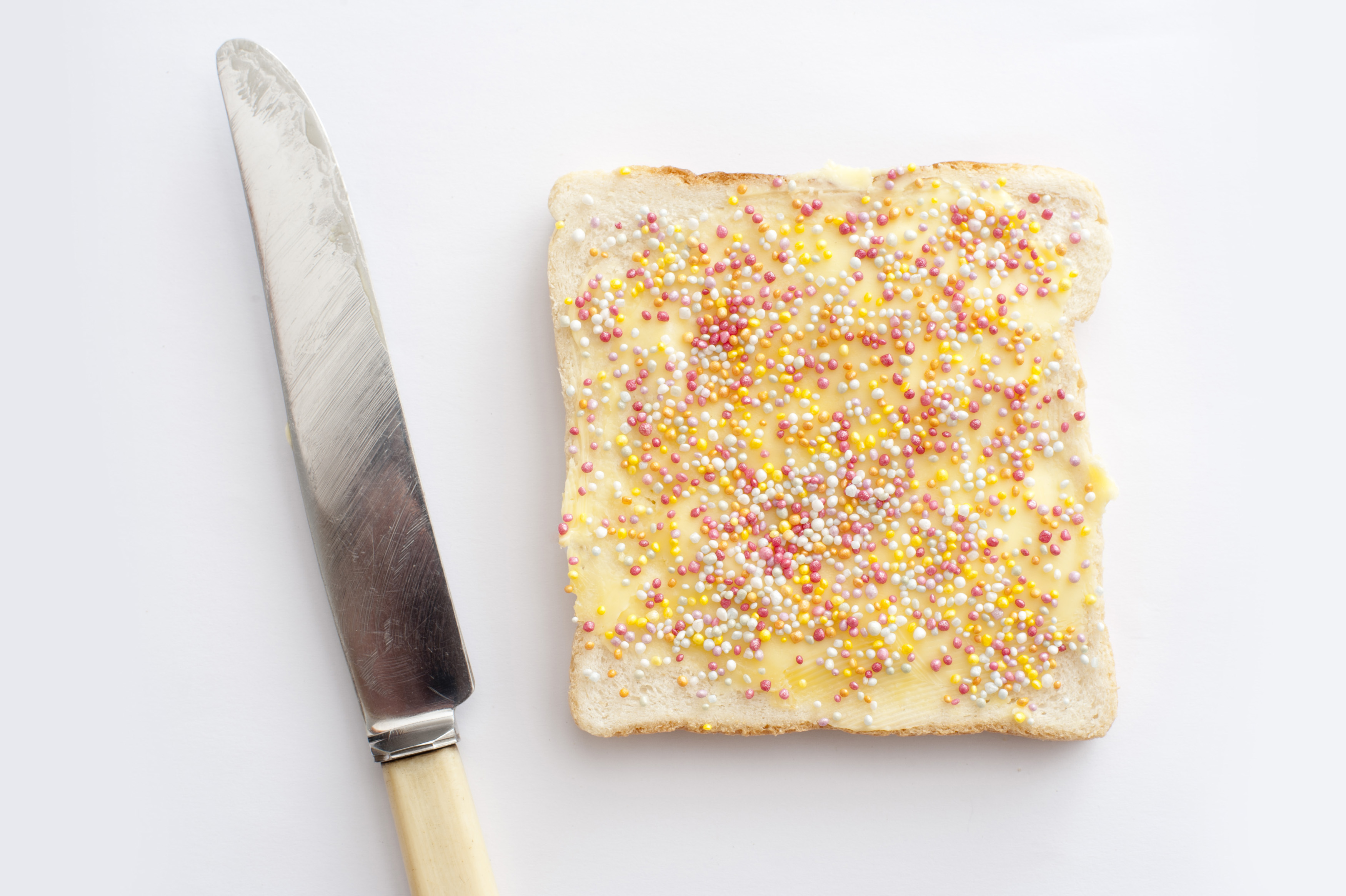 Single slice of party fairy bread with a topping of colorful candy sprinkles viewed from above alongside a knife on a white background