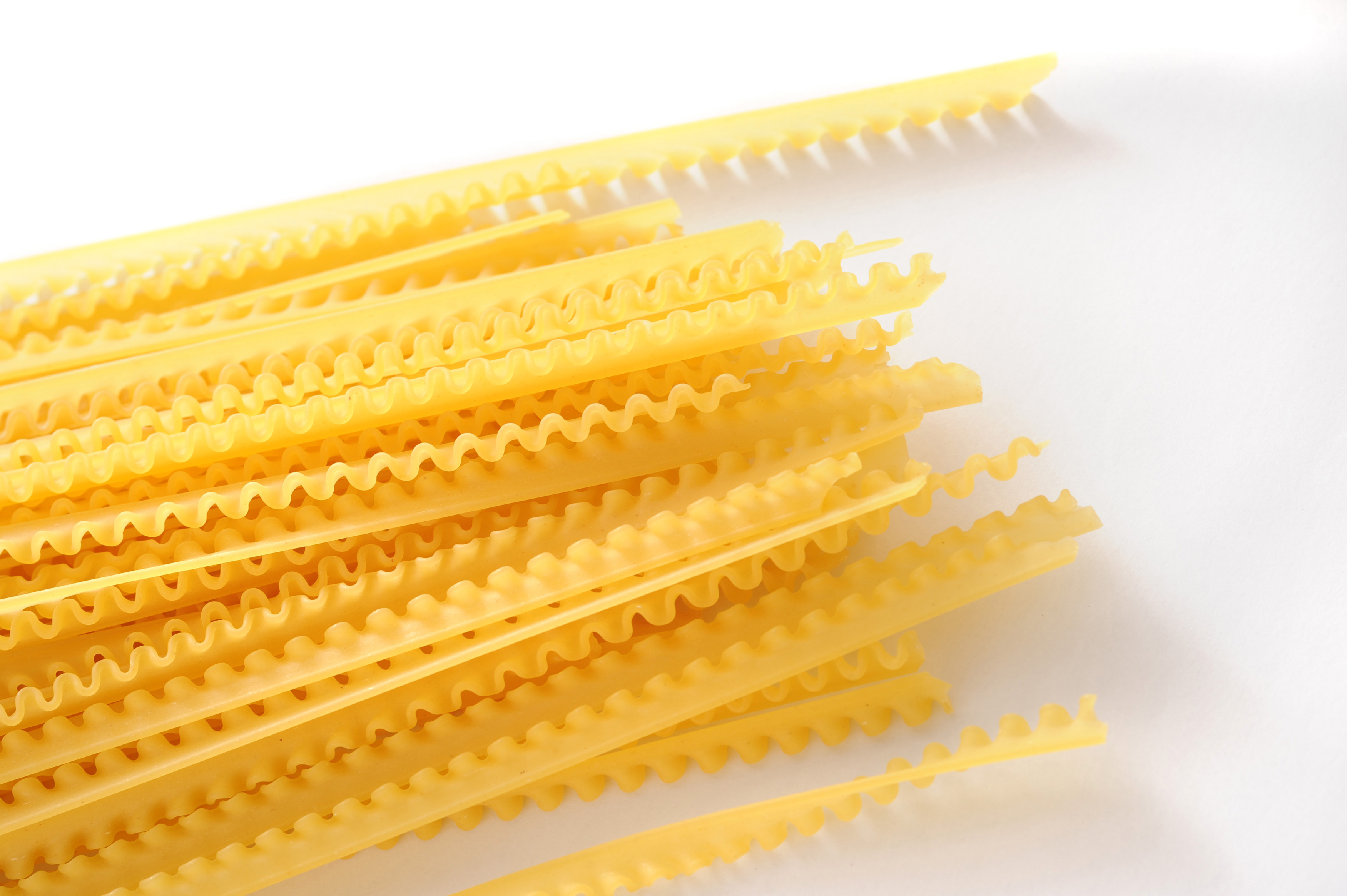 Uncooked noodles lying on white background. Daylight