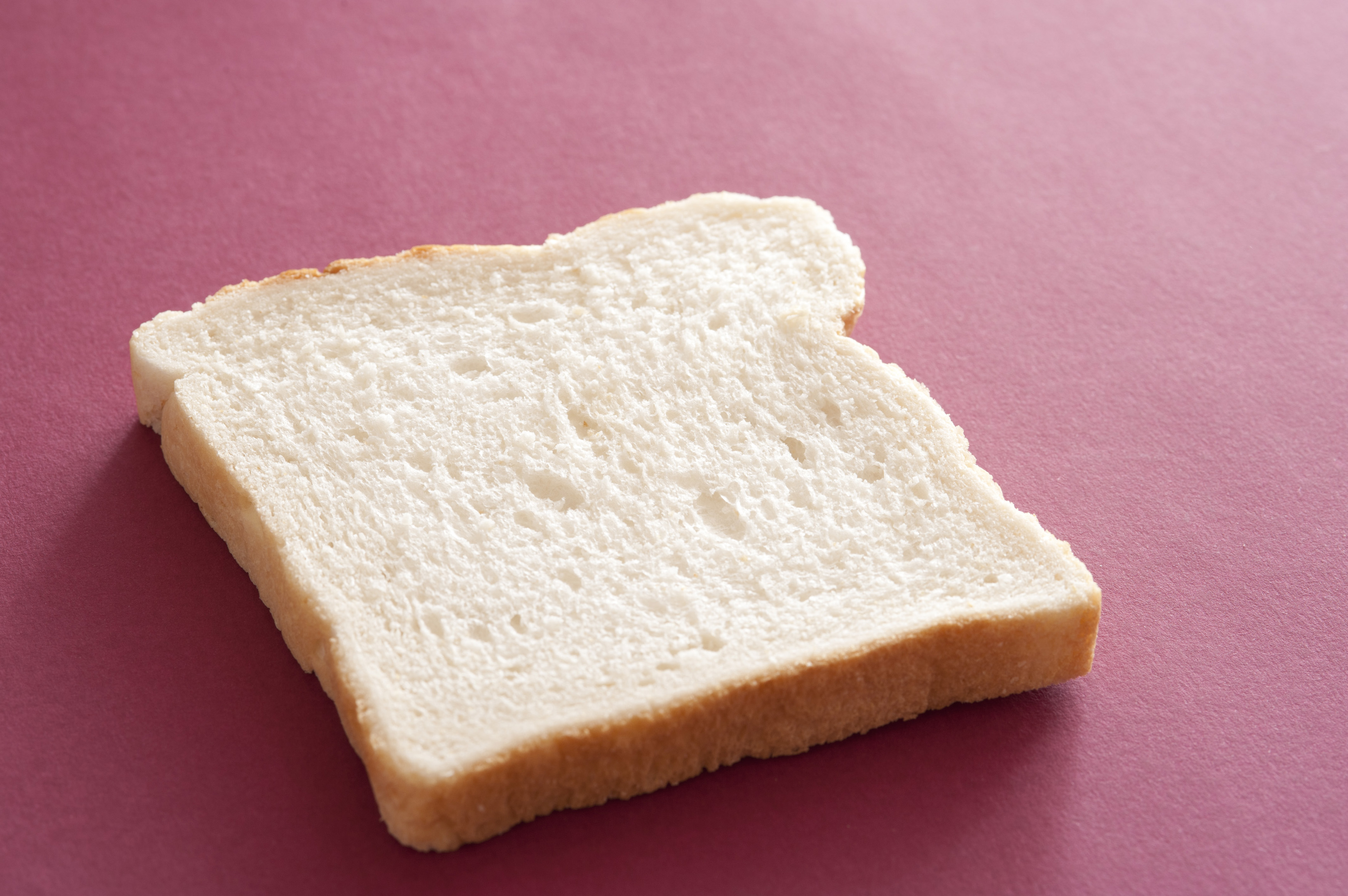 Slice of plain fresh white bread on a maroon background viewed low angle with copyspace