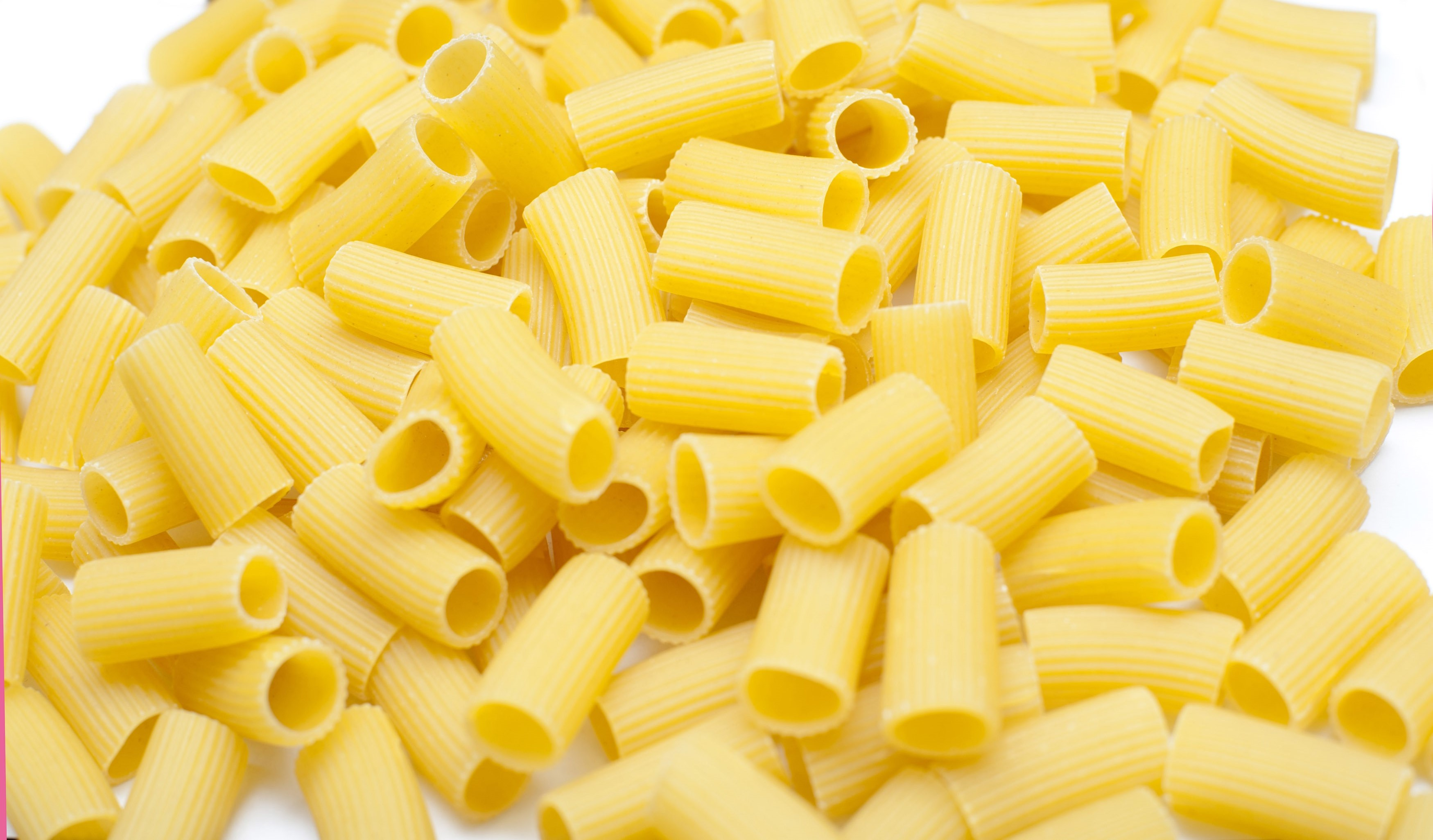 Close up background view of uncooked dried tubes of rigatoni pasta used as an ingredient in healthy Italian cuisine