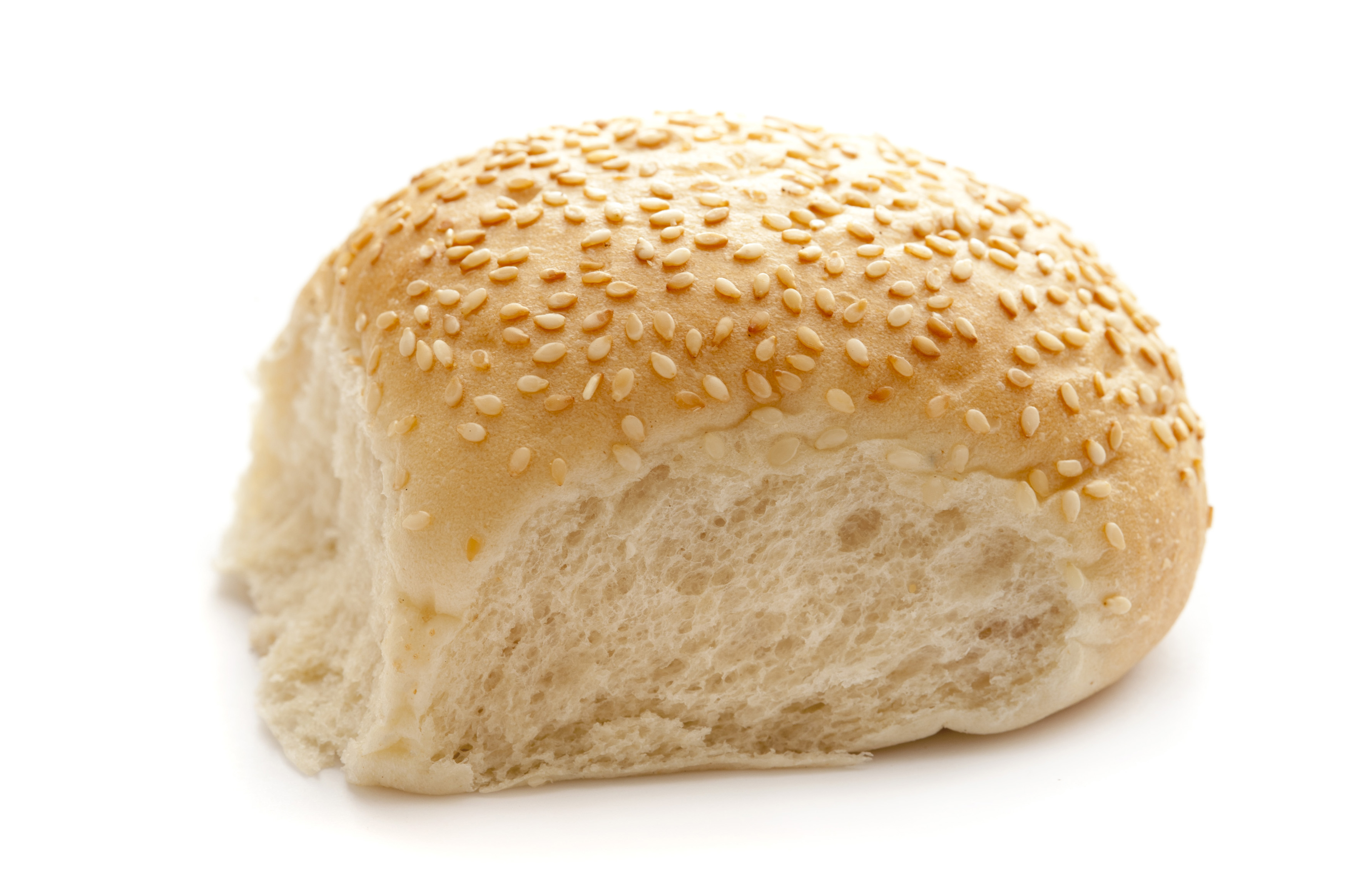 Freshly baked sesame roll with a crispy crust covered in sesame seeds over a white background, side view