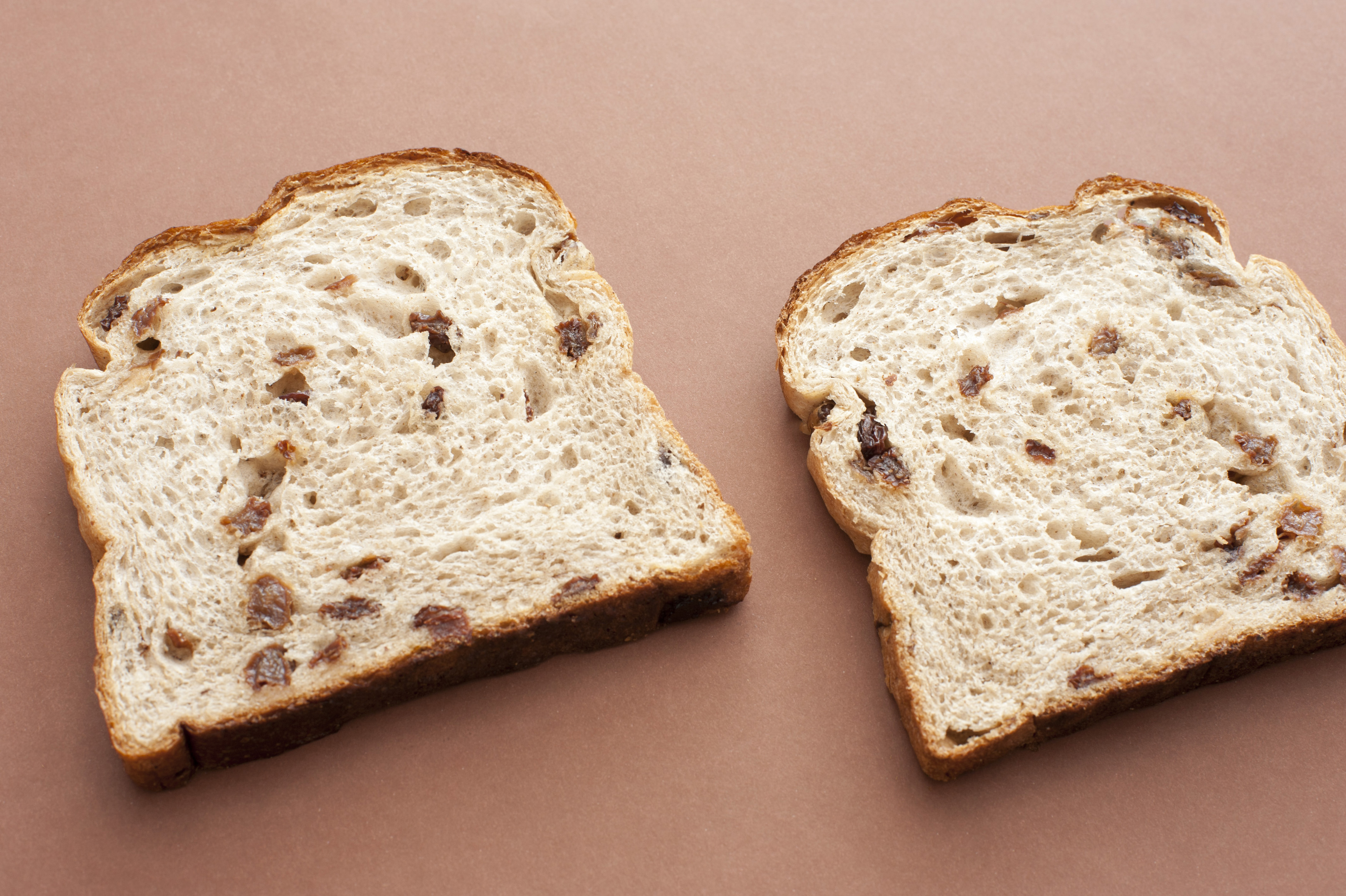 Close-up of two slices of bread with raisins lying on brown background