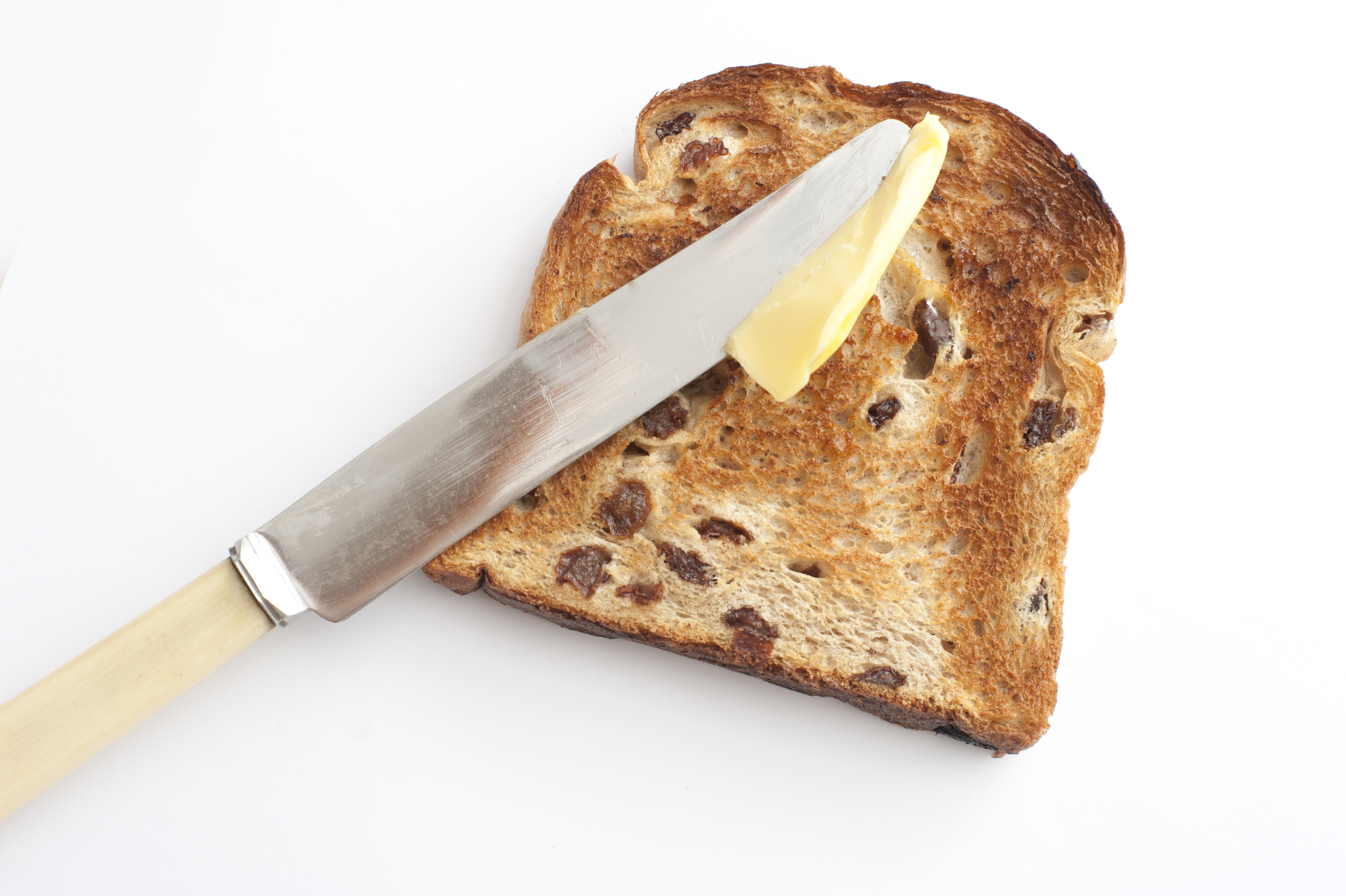 Spreading butter on a slice of hot fresh fruity toast with raisins using a bone handled knife, high angle view on white