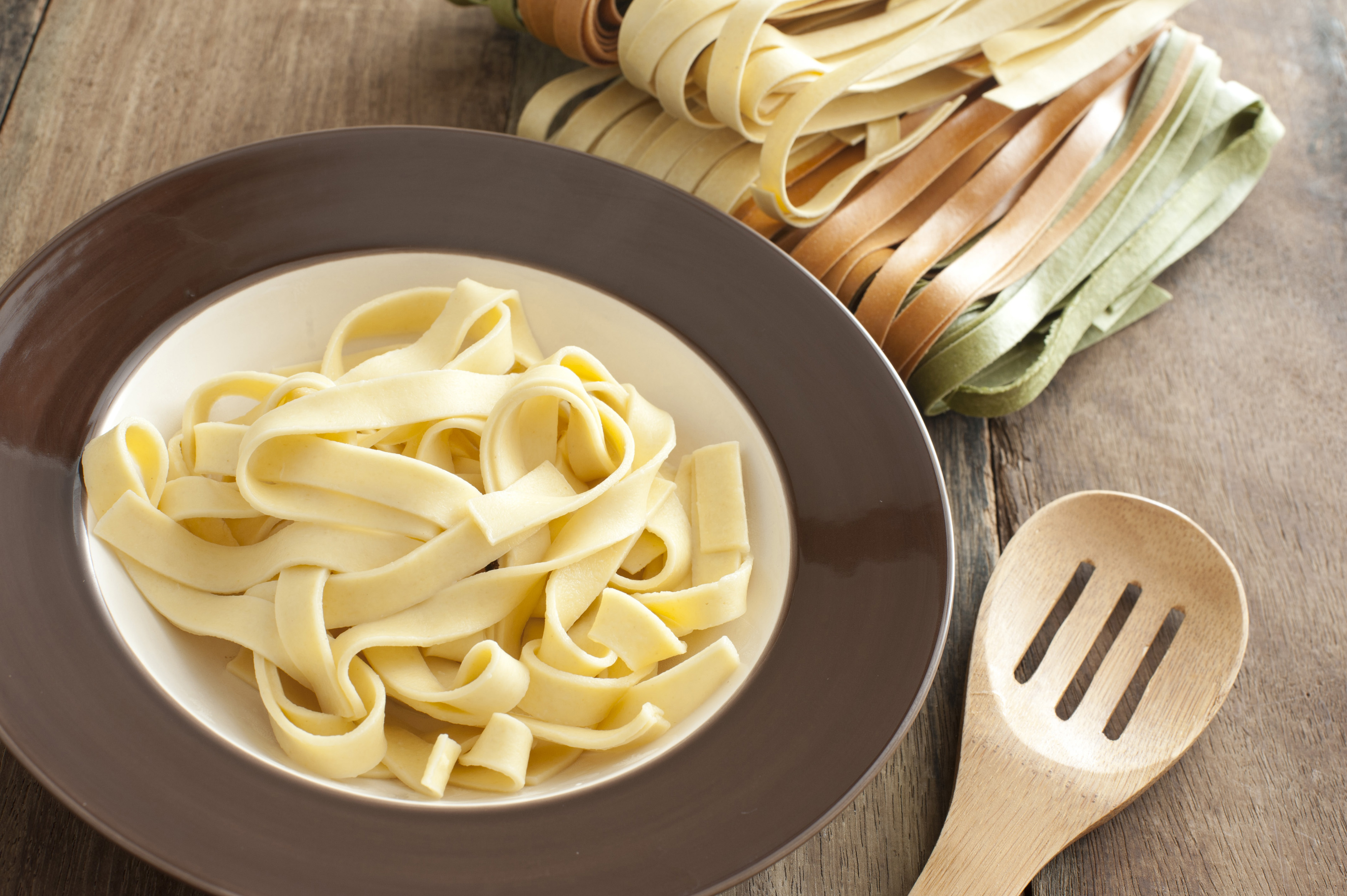 Close-up of spoon, plate with cooked fettuccini and raw noodles on brown wooden table