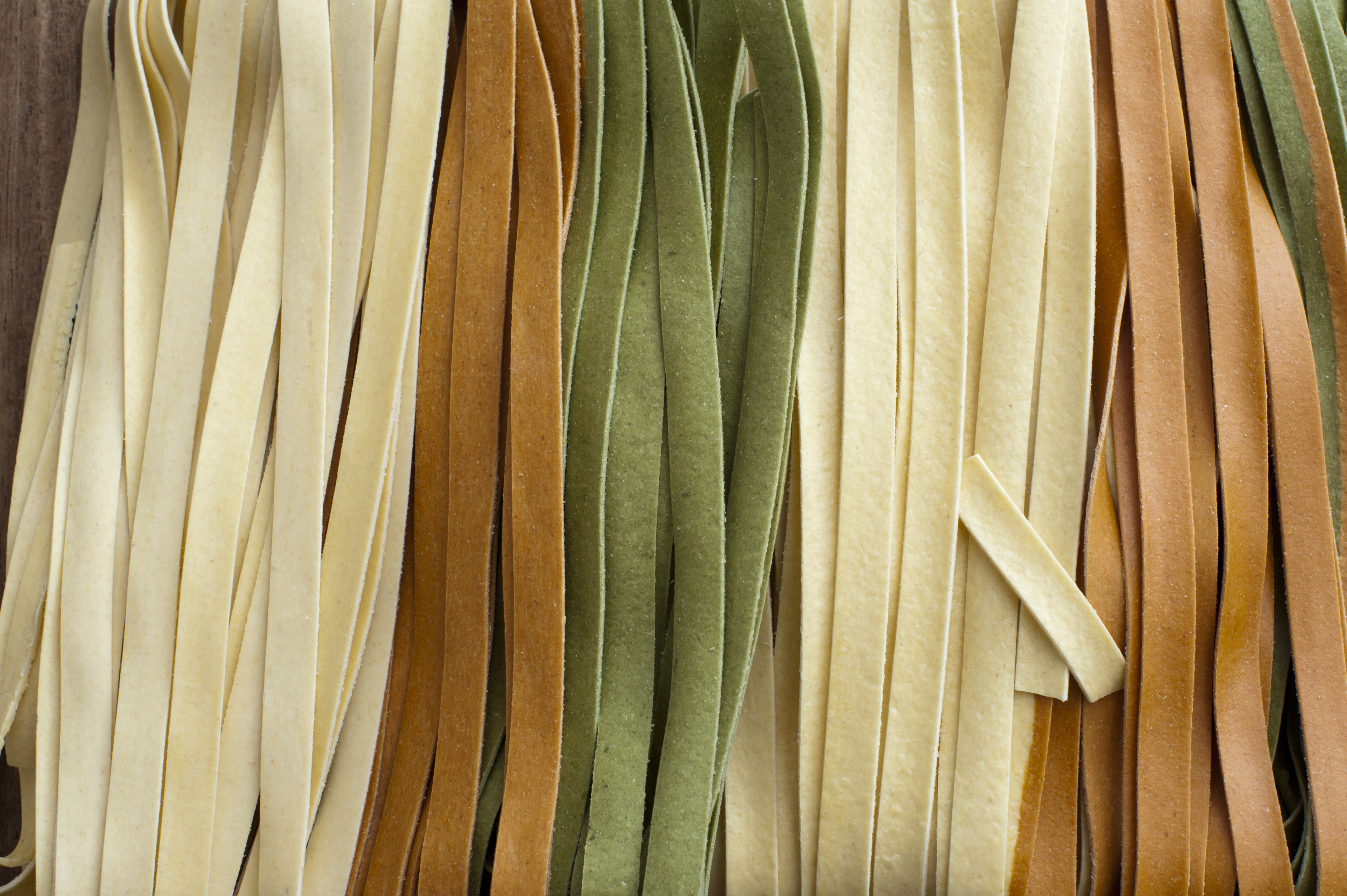 Background texture of colorful dried ribbons of tagliatelle pasta in white, brown and green for use in traditional Italian and Mediterranean cuisine