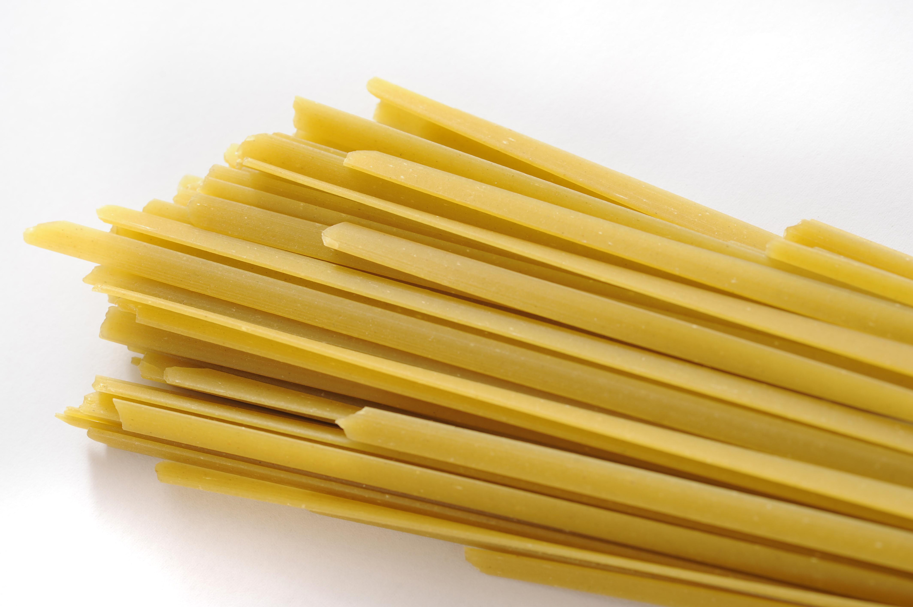 Bundle of traditional dried Italian tagliatelli pasta for use in Mediterranean cuisine on a white background with copyspace