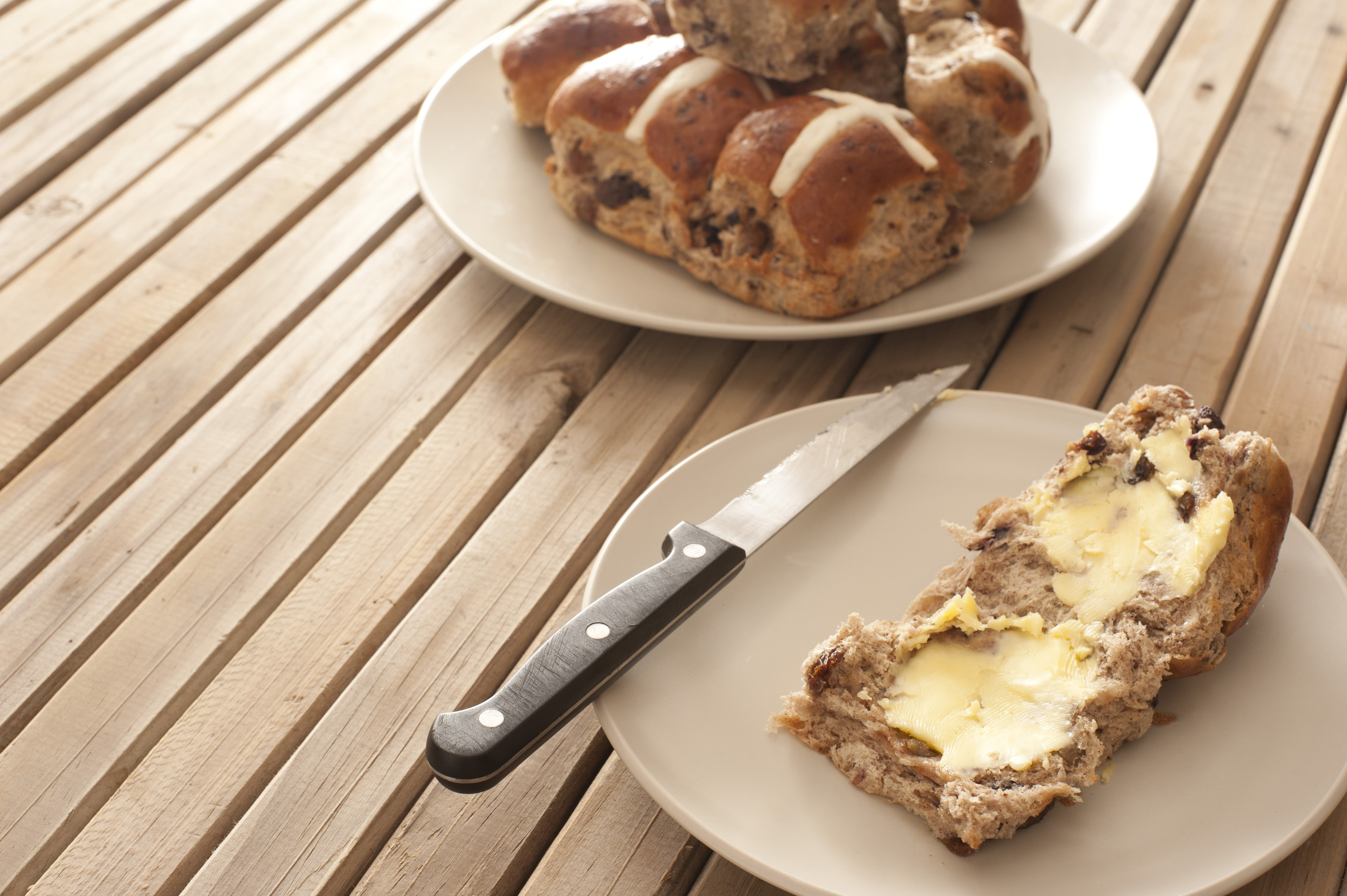 Buttered Easter Hot Cross Bun with fruity raisins served on a side plate ready for a tasty refreshment at teatime, wooden slatted tale with copyspace