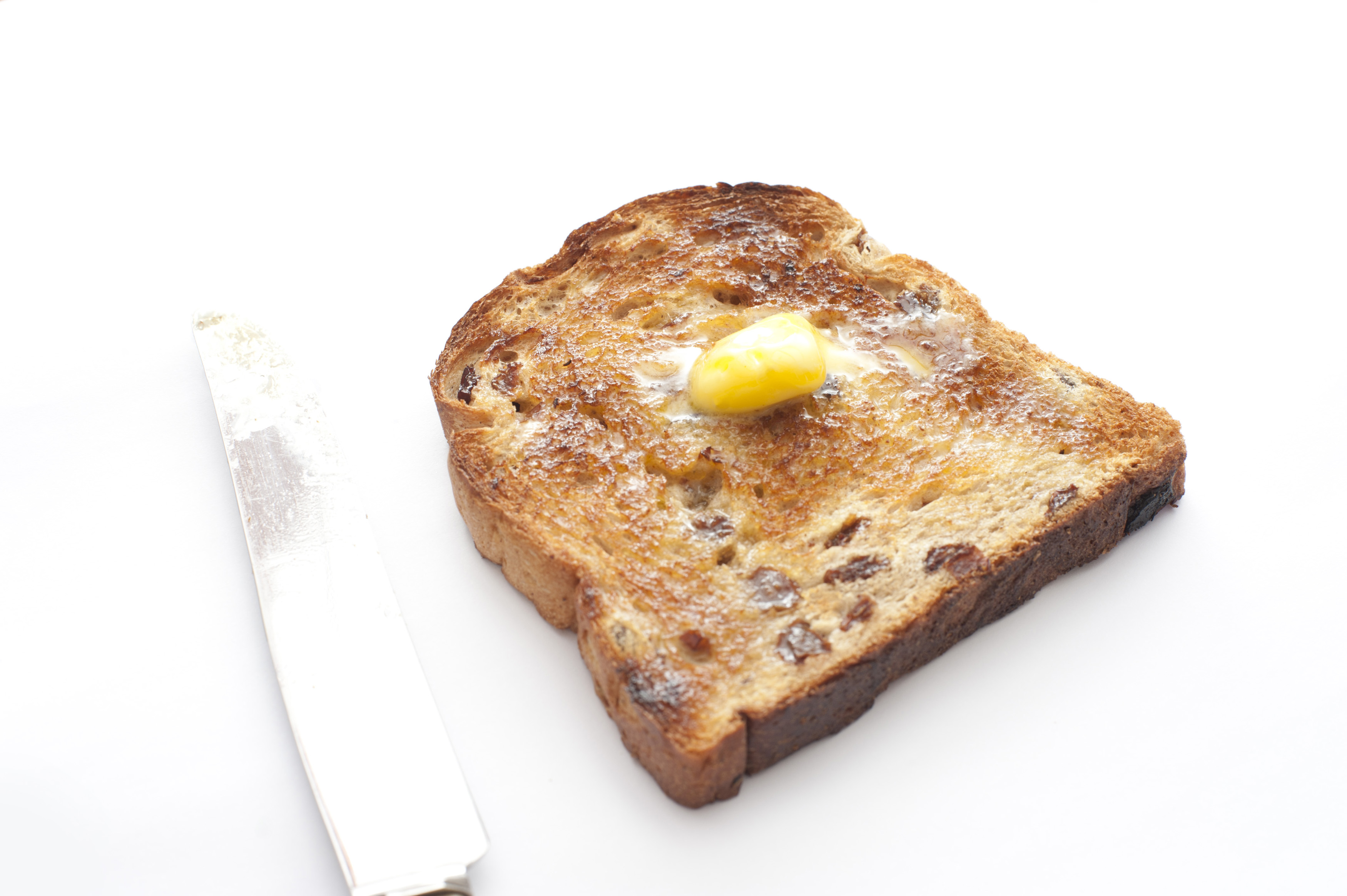 Slice of hot fruity toast with raisins and a dollop of melting butter on top on a white background, high angle view