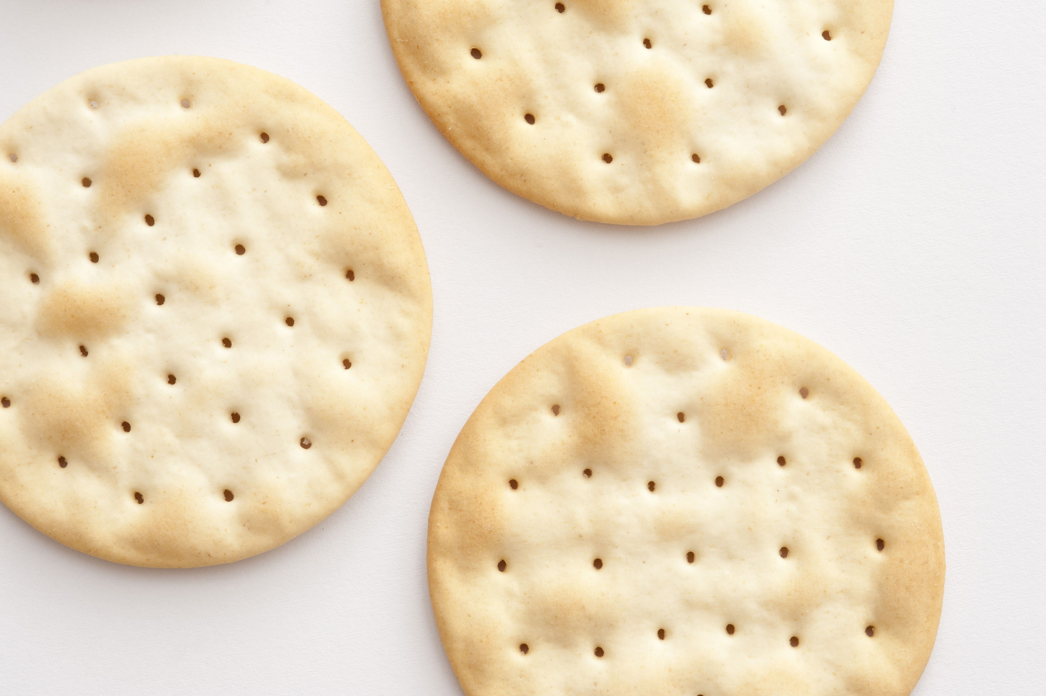Water crackers background with an overhead view of plain crispy water biscuits made from flour and water served to accompany a cheese platter, on white