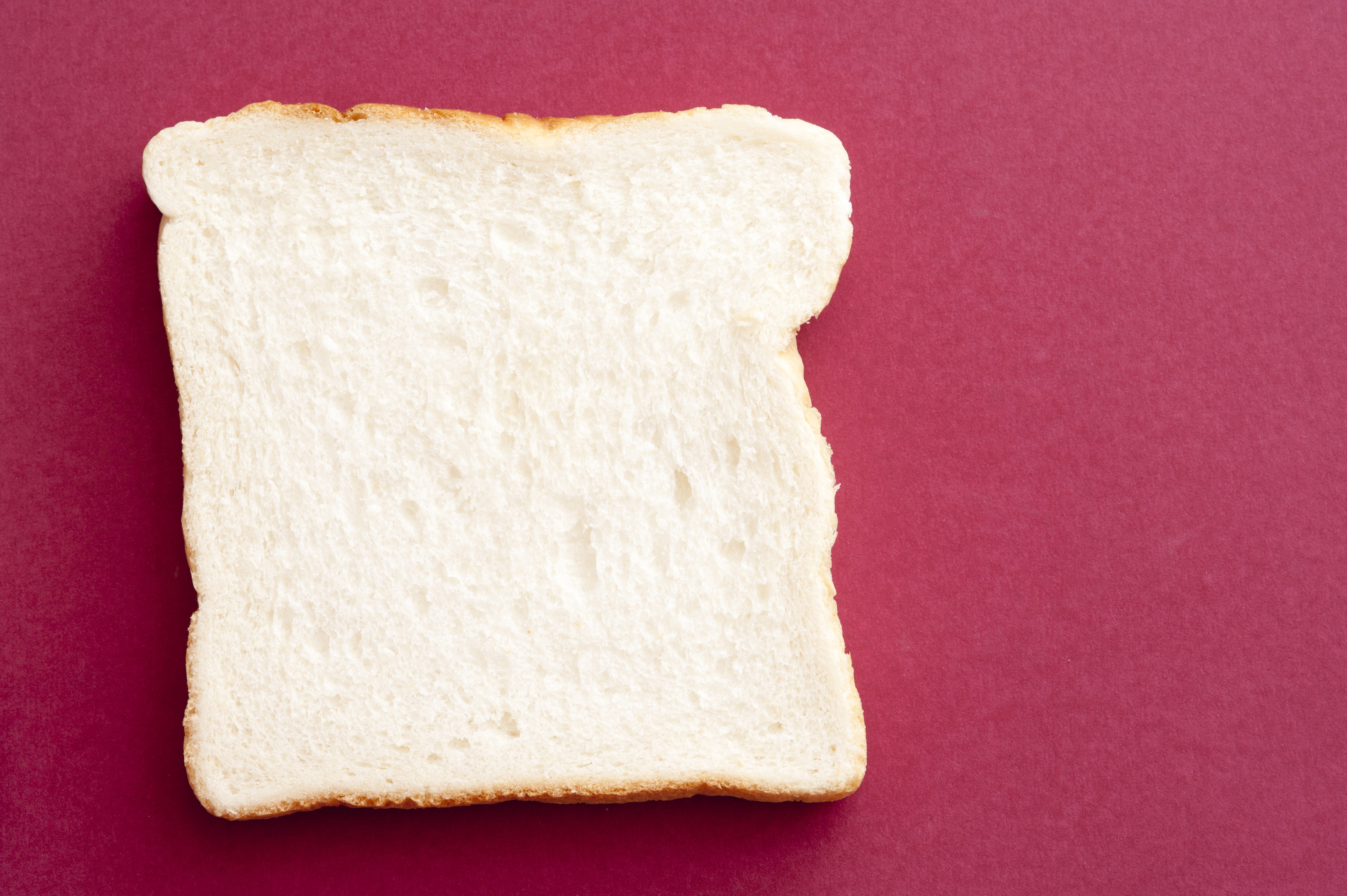 One slice of white bread on pink background