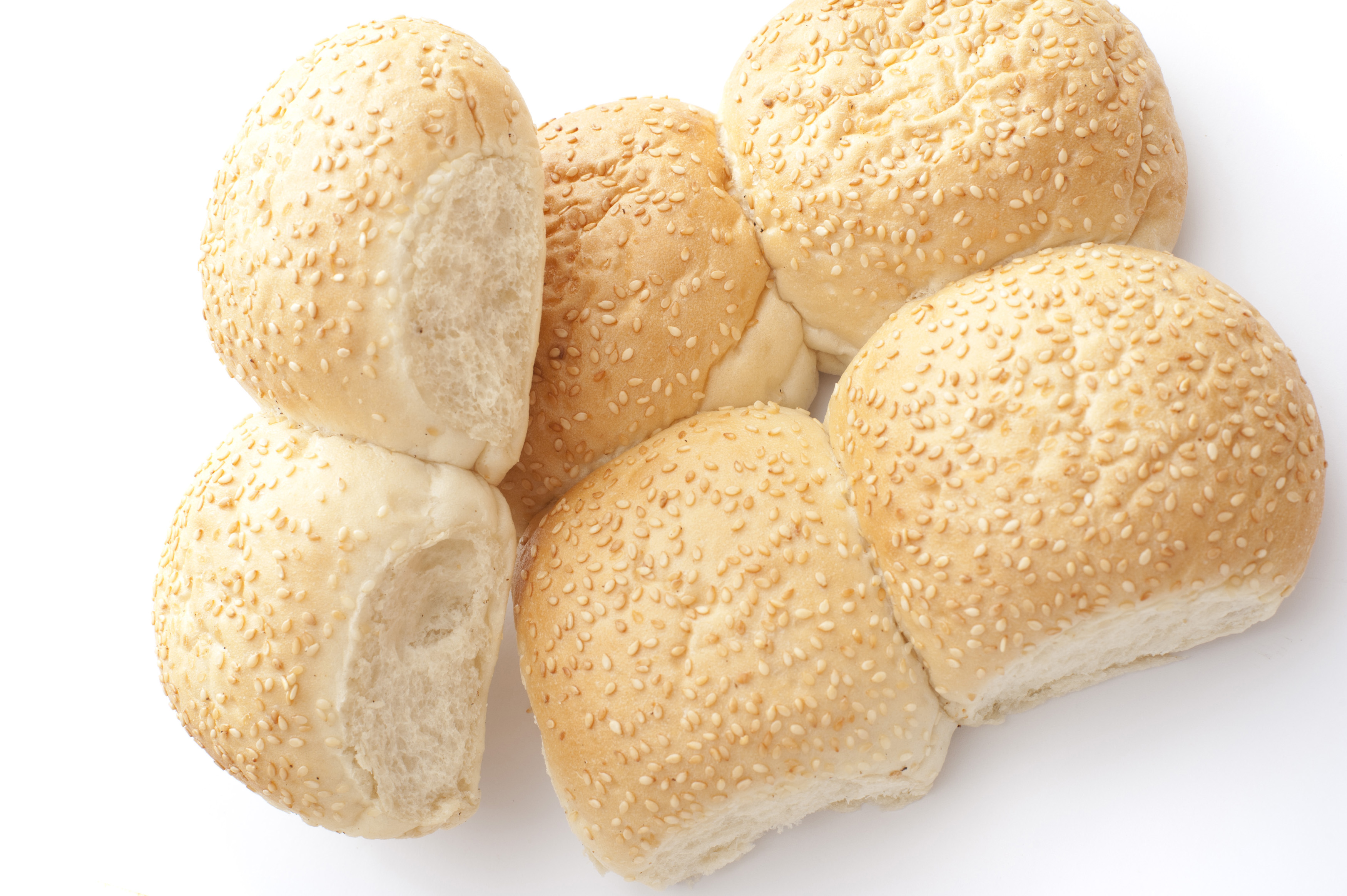 Batch of fresh joined sesame rolls from a bakery with two broken off to show the texture of the bread viewed overhead on white