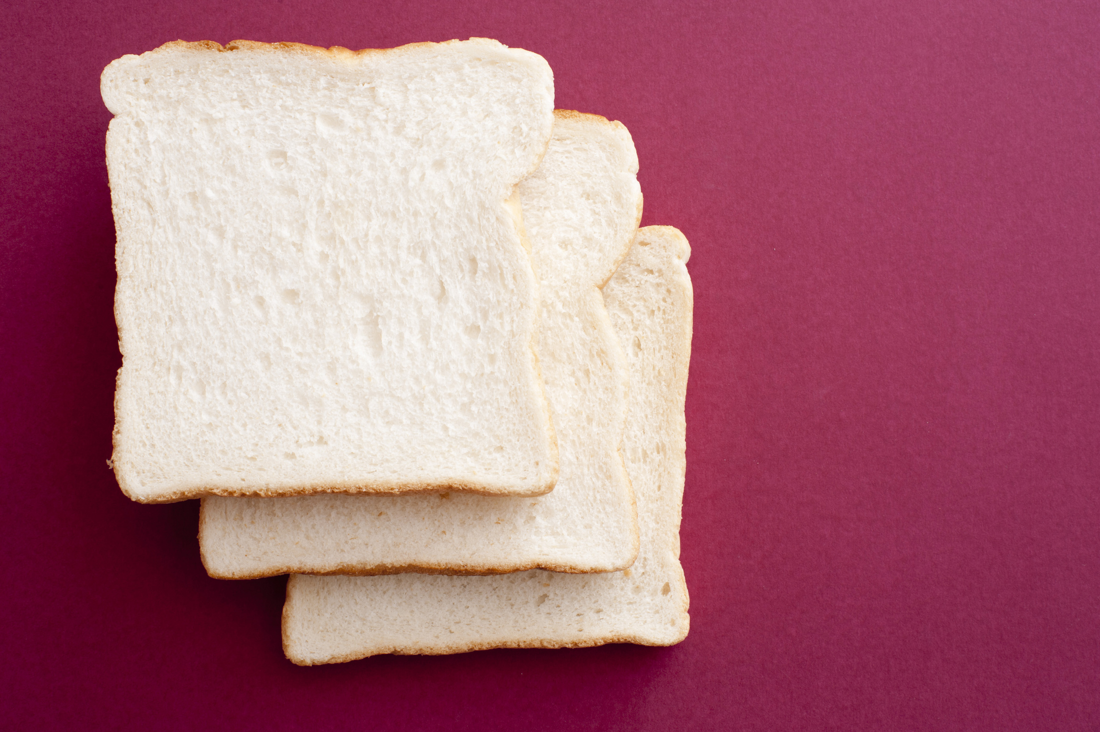 Photo of three white bread slices against of purple background