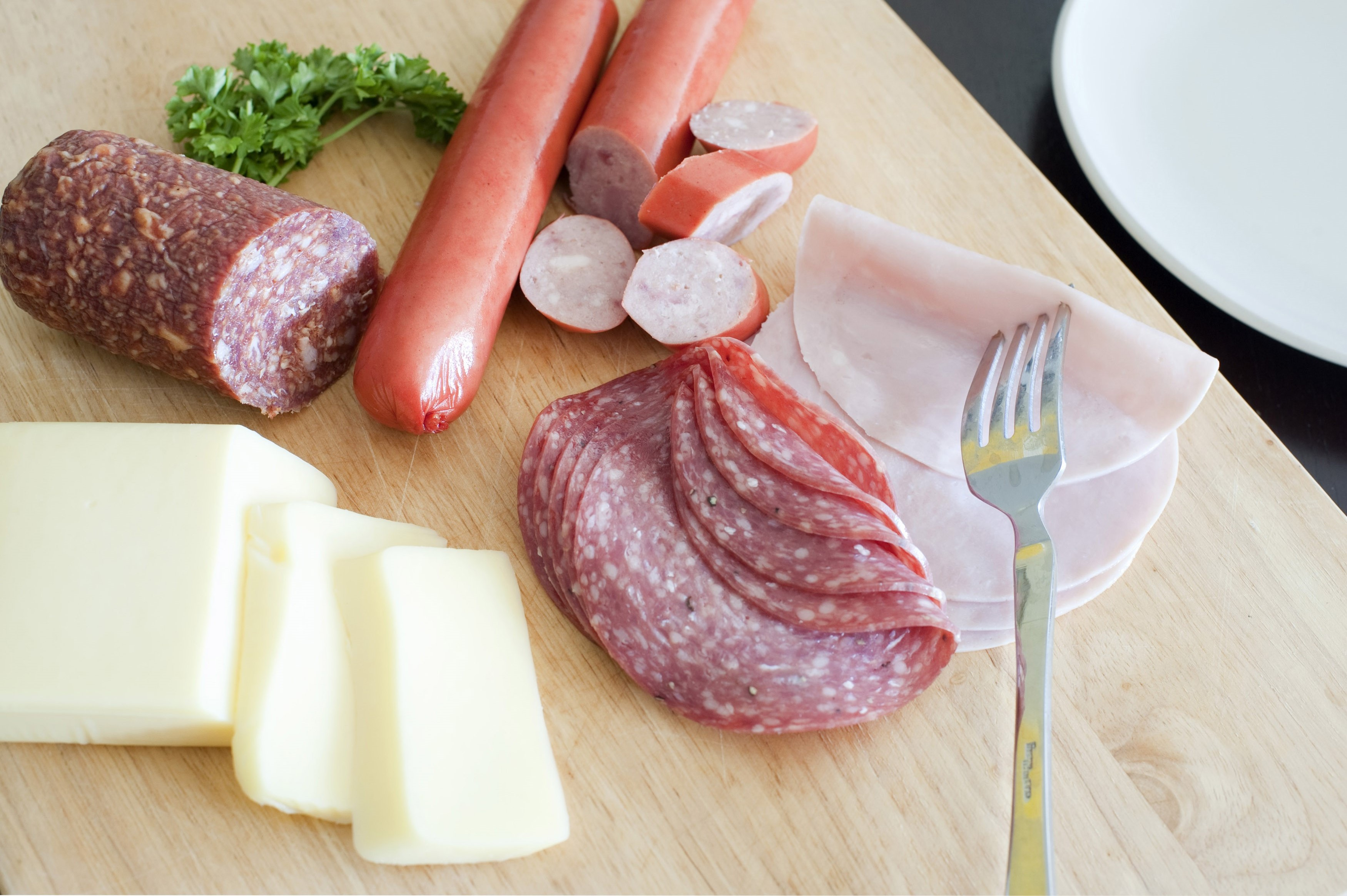 Wholesome traditional German breakfast with sliced cold meat, spicy salami, sausages and cheese served on a wooden chopping board