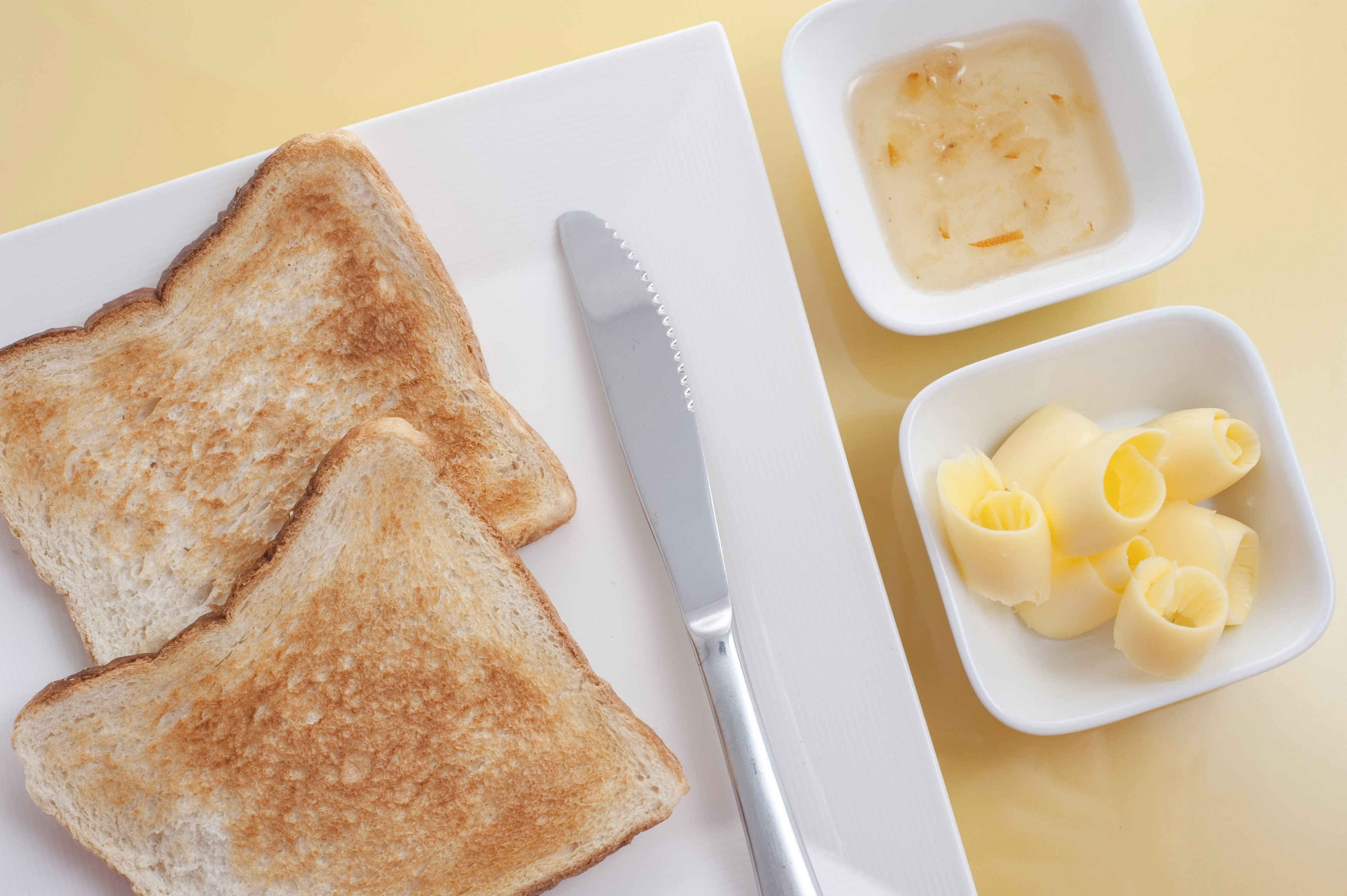 Overhead view of a serving of sliced white toast with butter and marmalade on the side in individual dishes