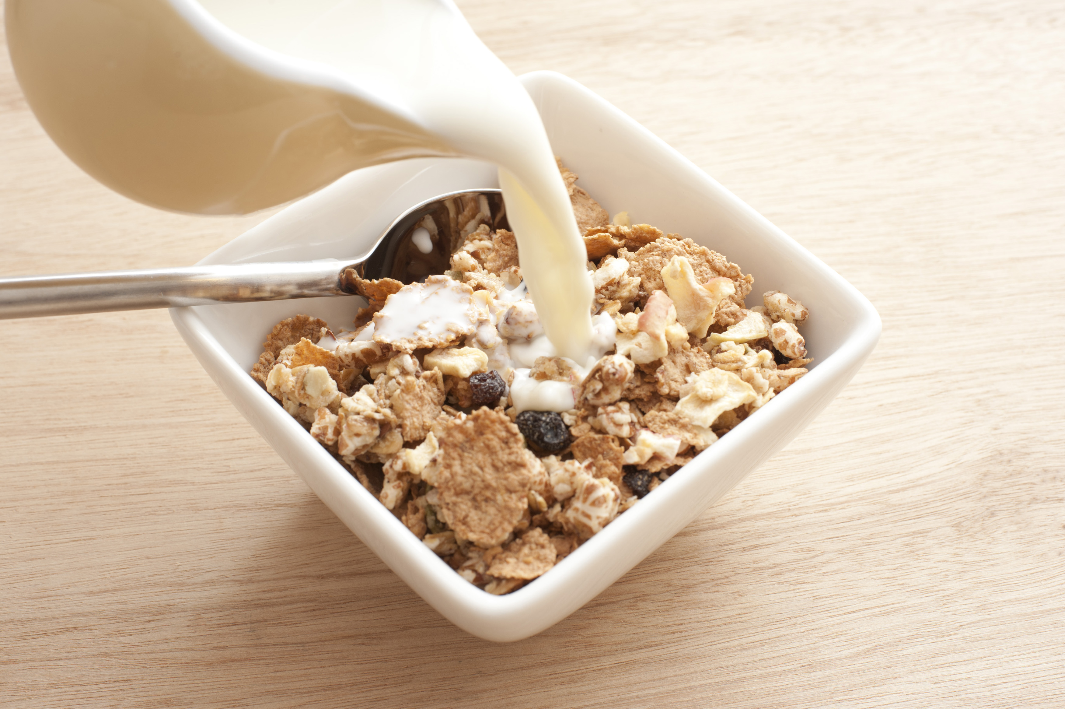 Pouring milk into healthy breakfast cereal of bran flakes with raisins served in a square bowl