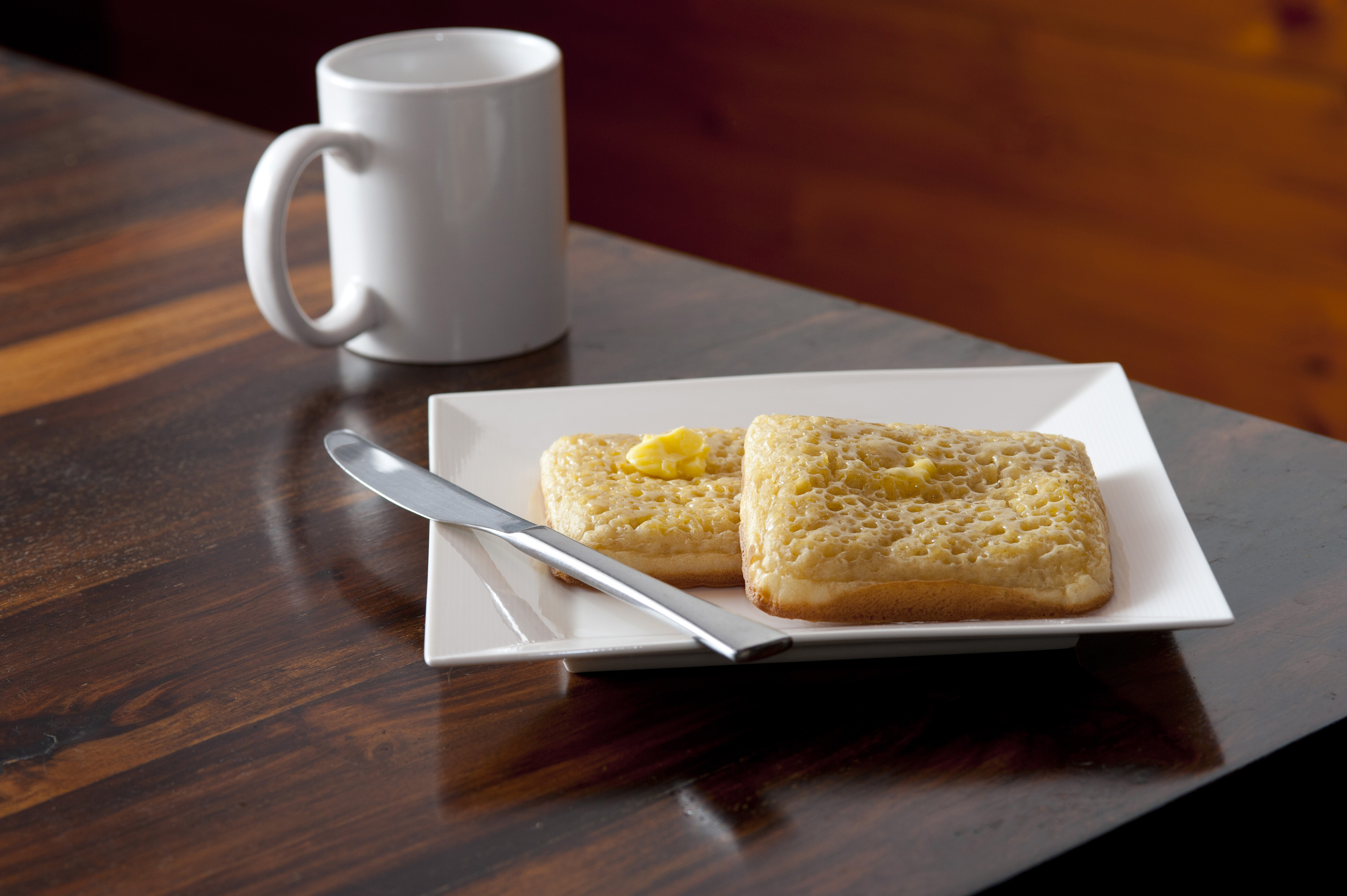 Coffee mug next to square plate with two crumpets and a stainless steel knife placed on the corner of a wooden table