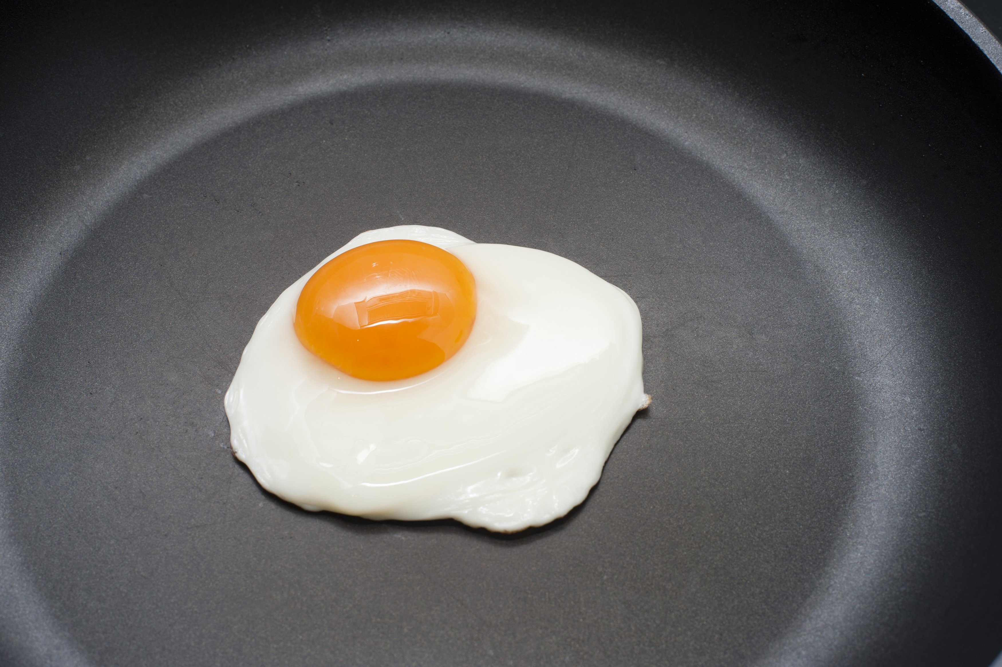 Single fried egg with a delicious deep yellow yolk in a non-stick frying pan ready to be served for breakfast