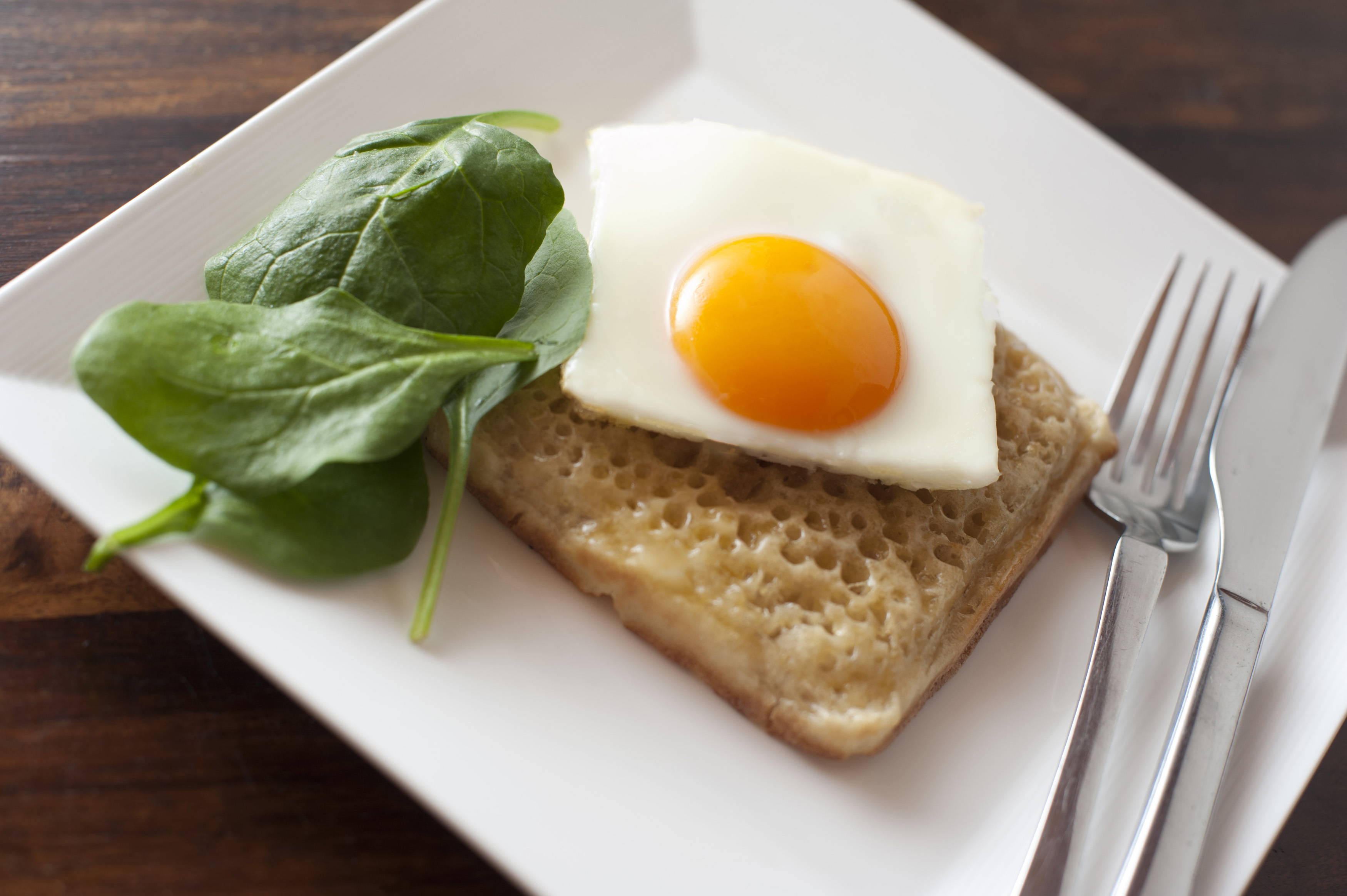 Close up of square egg sunny side up on a crumpet besides fresh spinach leaves and utensils on a white plate