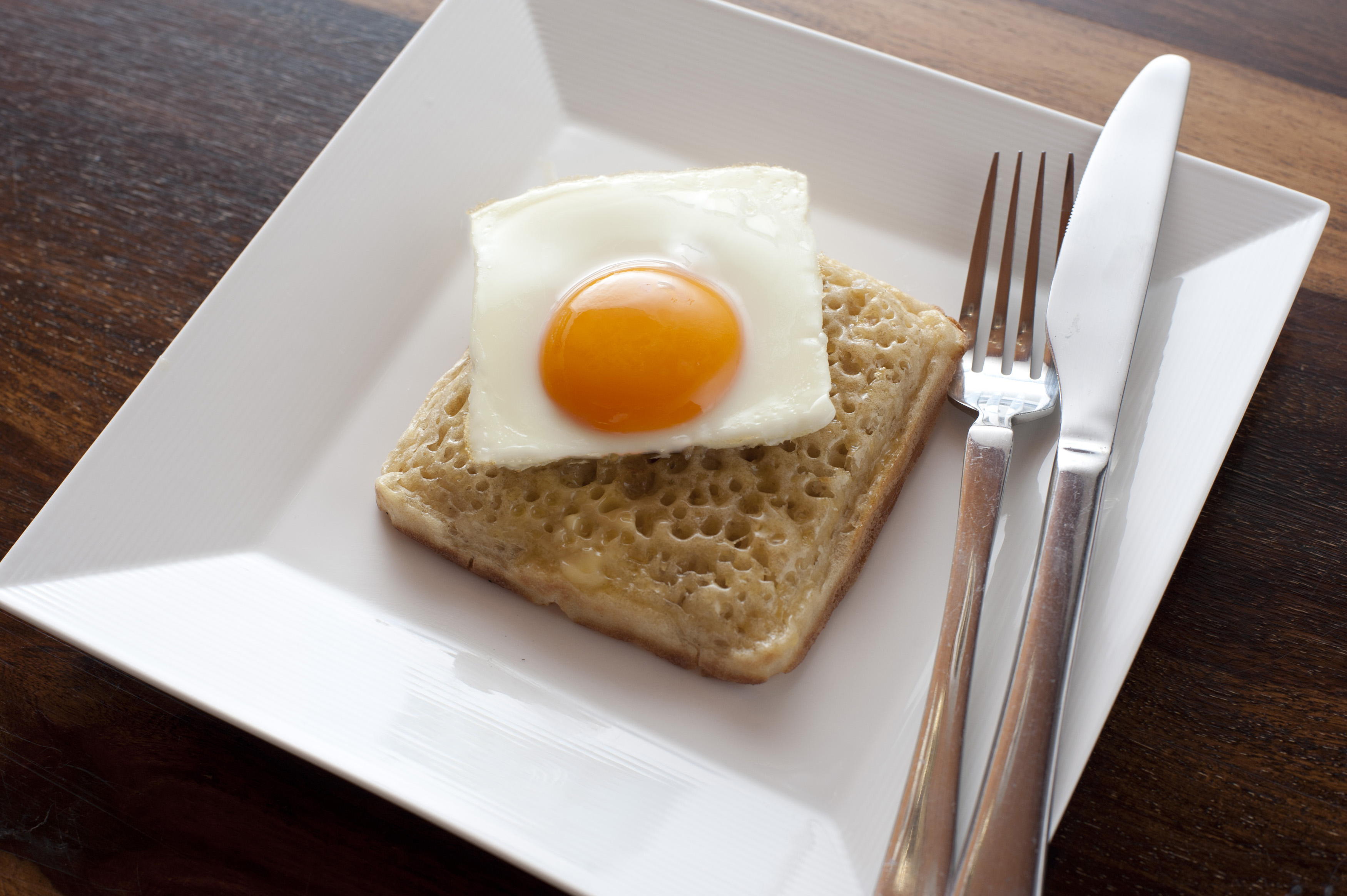 Sunny side up egg cut as square on top of matching shaped fried crumpet patty and plate with fork and knife on top