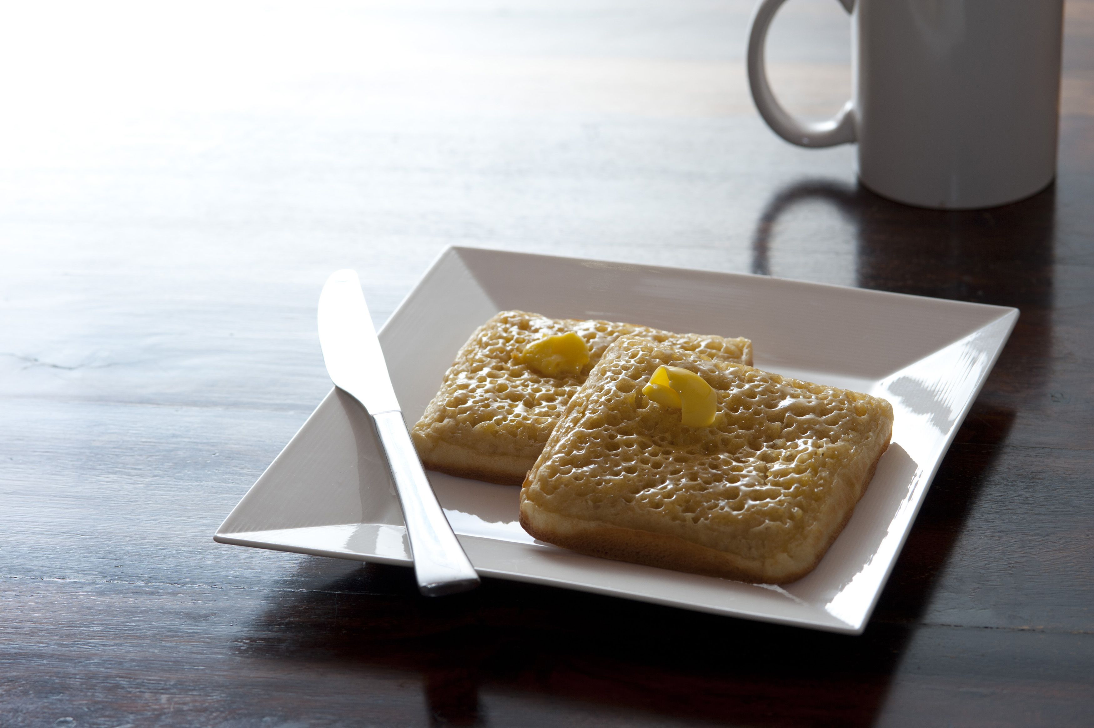 Bright light behind single square plate of crumpets on table with butter knife and coffee mug nearby