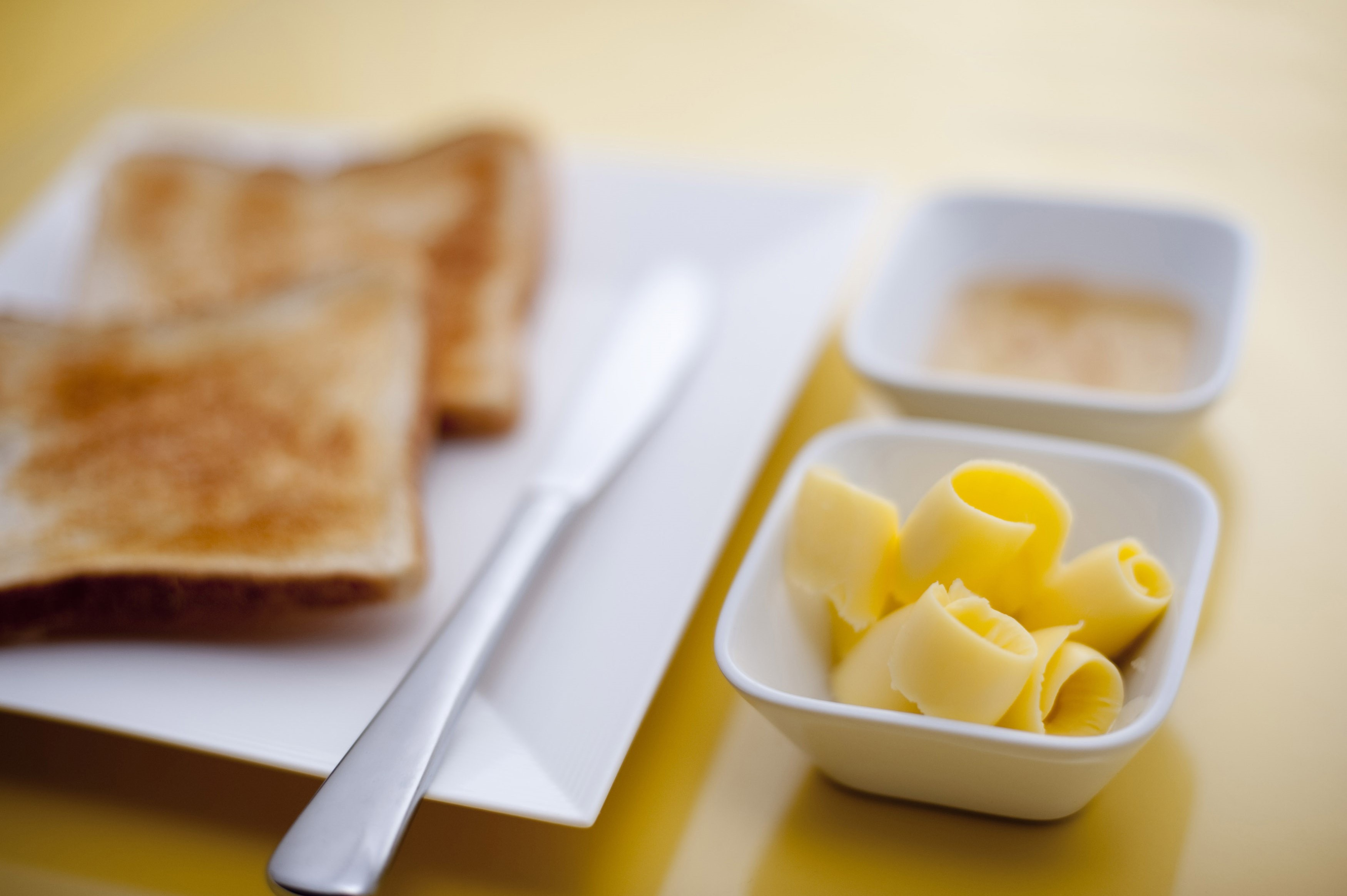 Toast with butter curls and marmalade laid out in individual containers on a wooden chopping board for a tasty breakfast