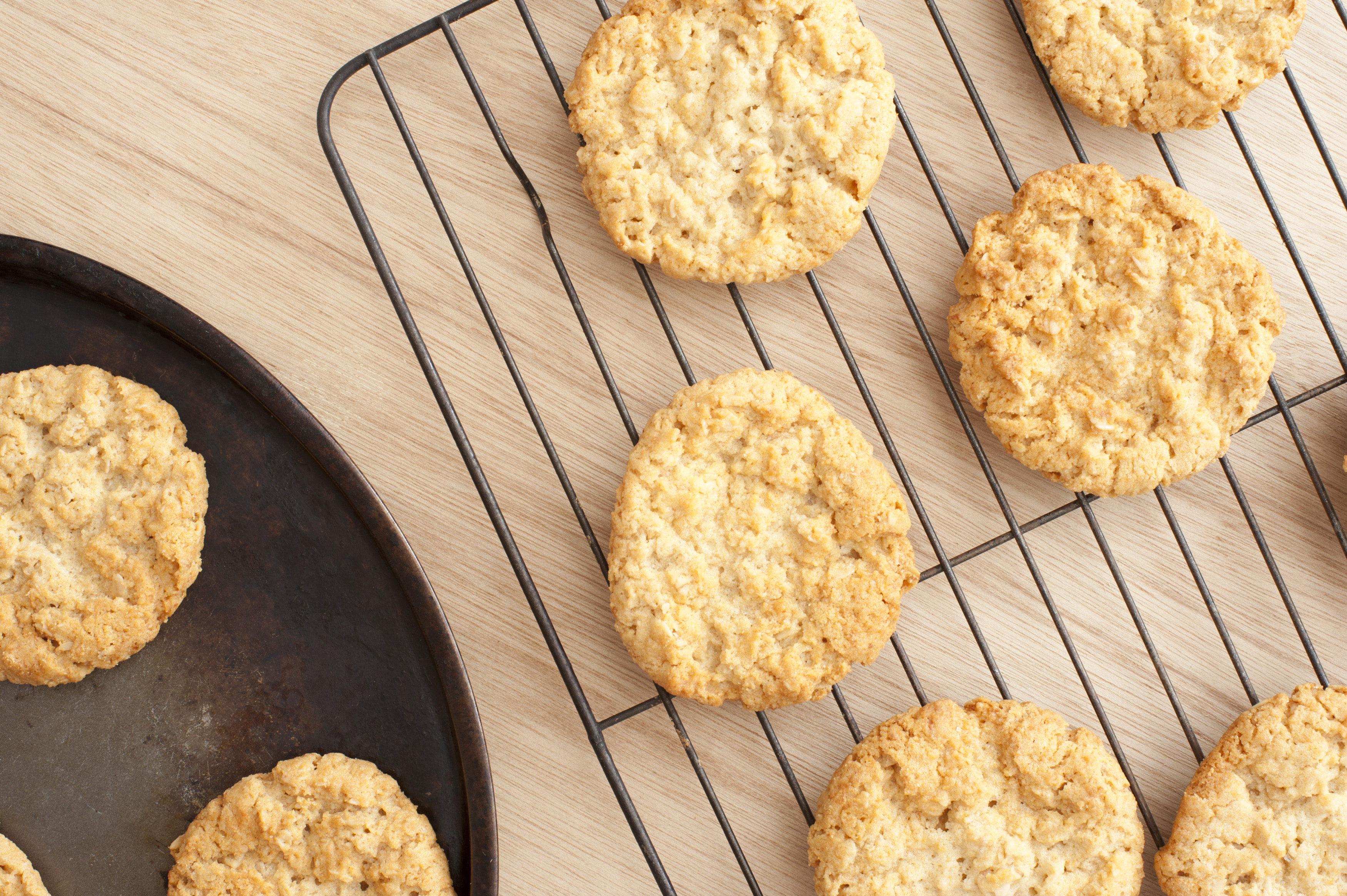 Delicious home baked crispy oat cookies cooling on a wire rack on a wooden kitchen counter, overhead view