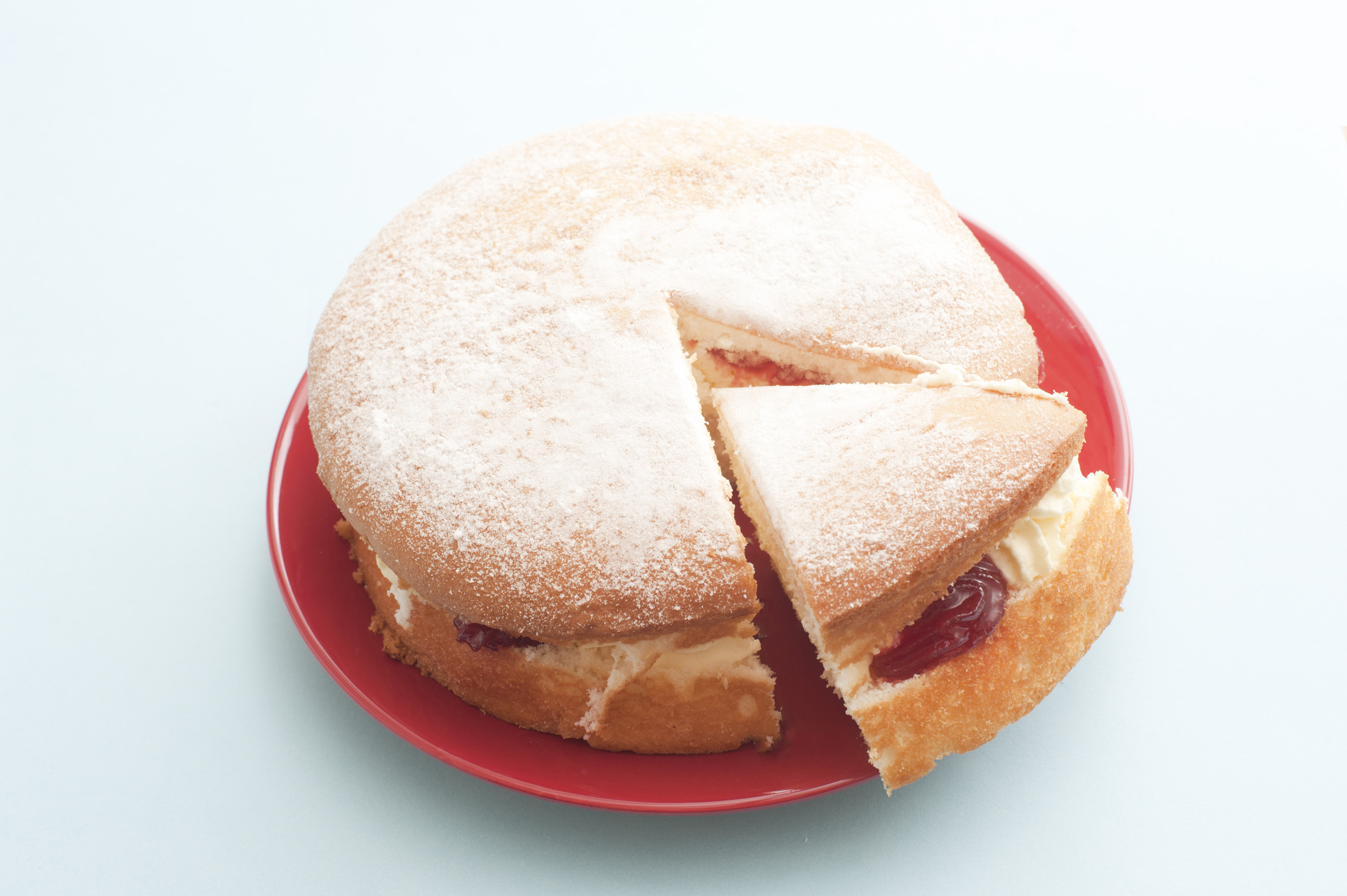 Freshly baked sponge cake filled with cream and strawberry jam served with one cut slice on a red plate