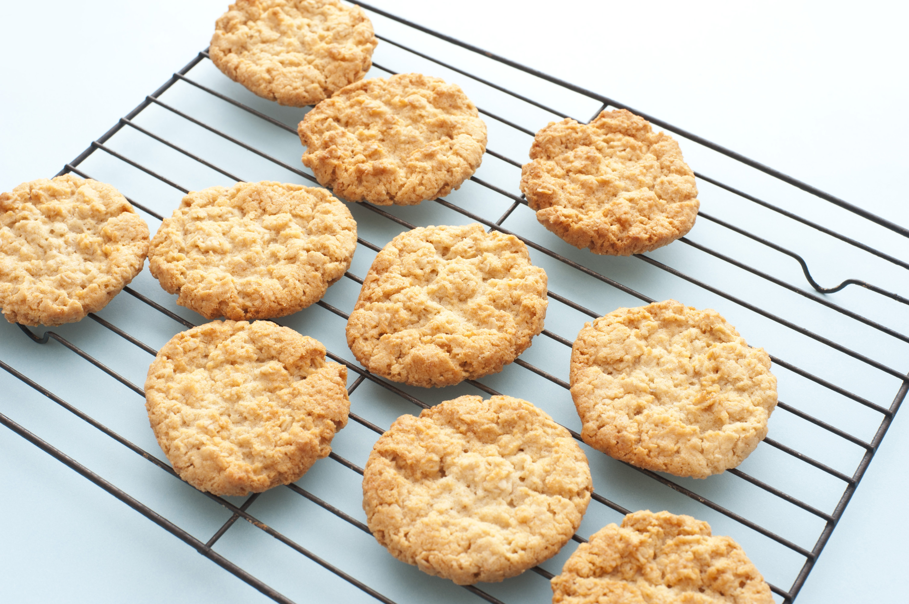 Freshly baked crispy golden oat cookies cooling on a wire rack in the kitchen after removal from the oven, high angle view on white