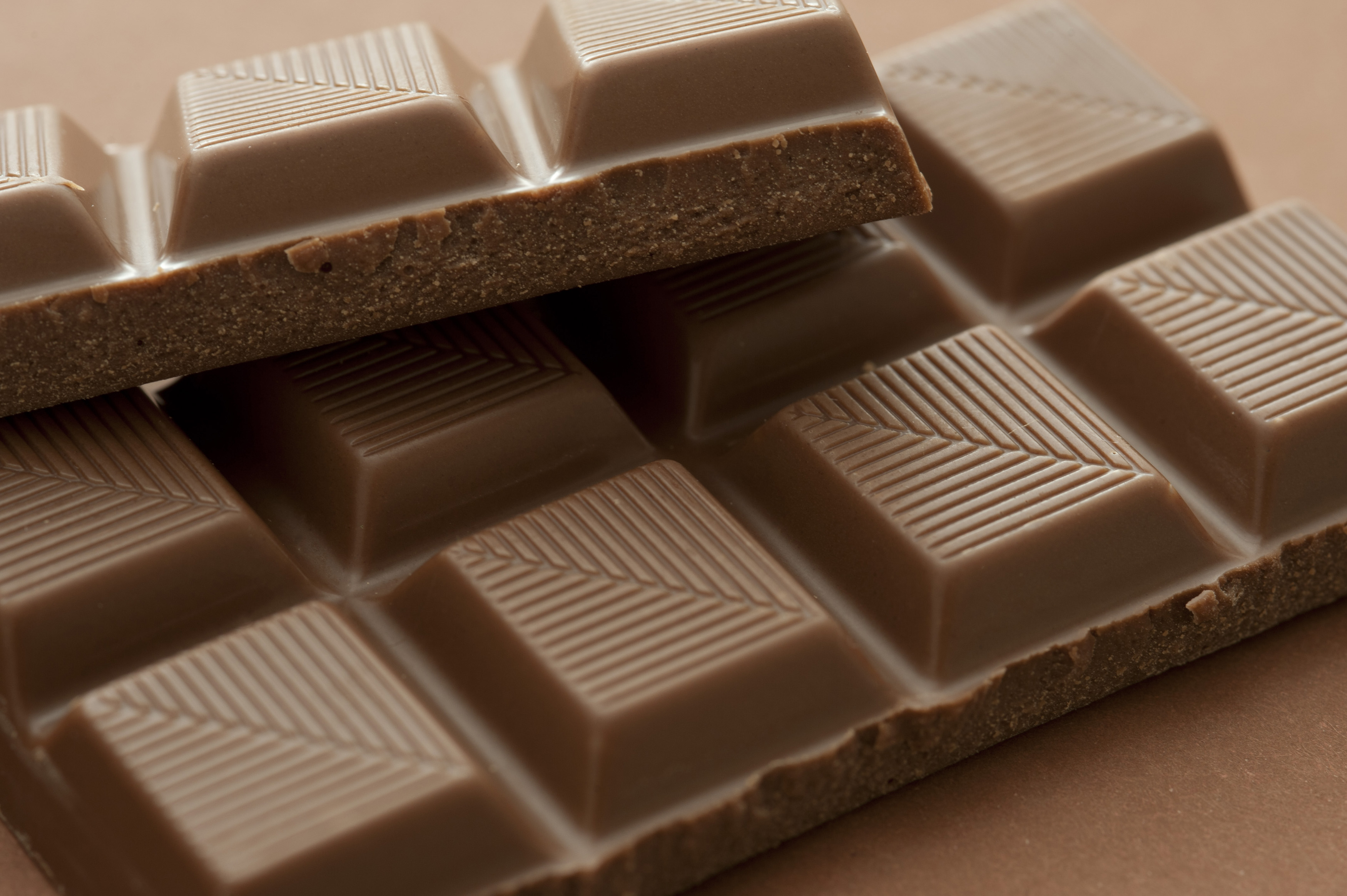 Bar of milk chocolate with pattern detail on the individual squares of converging lines in a close up view