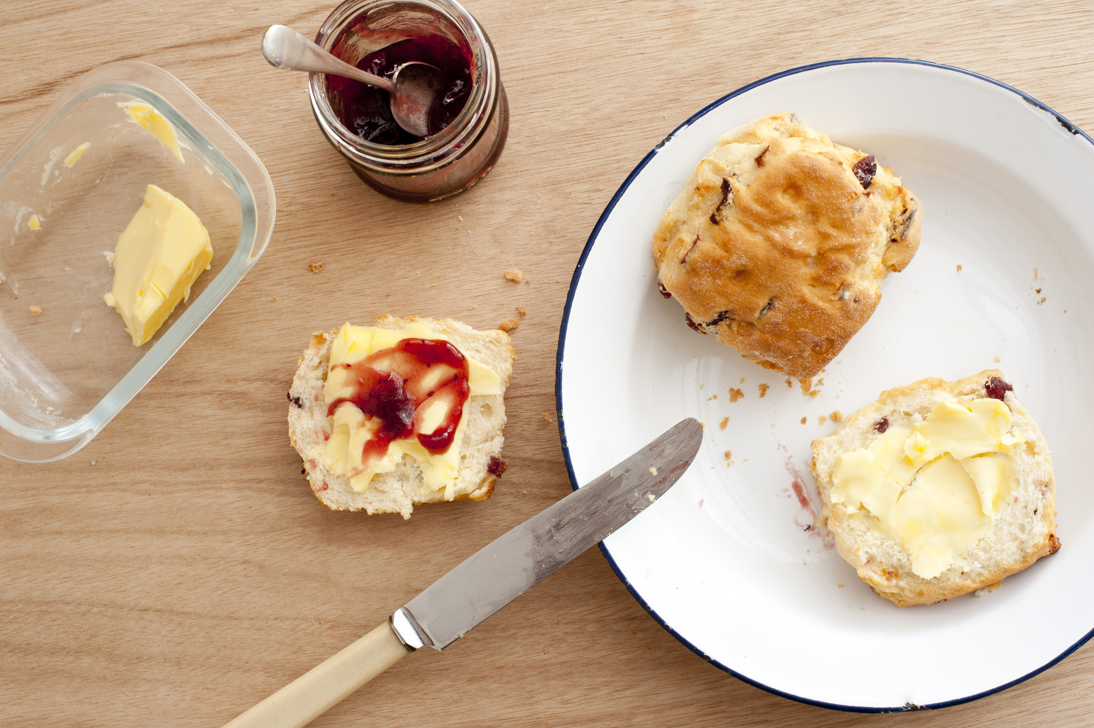 First person perspective view looking downward at two baked scones with butter, fruit jam and knife over wooden table