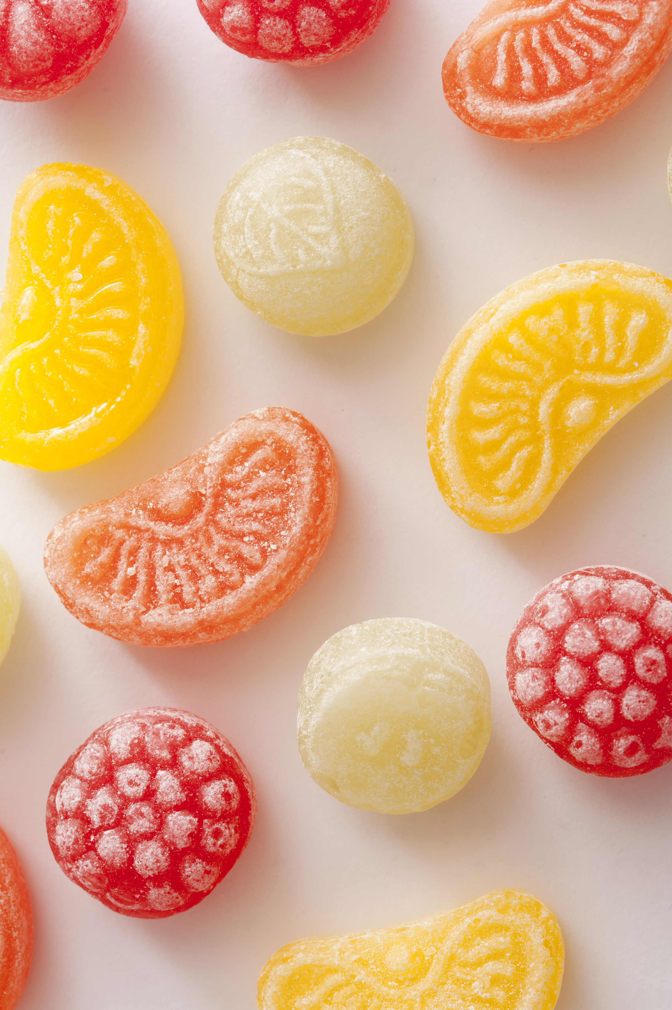Colorful background of sugar coated jelly candy fruits arranged on a white background and viewed from above