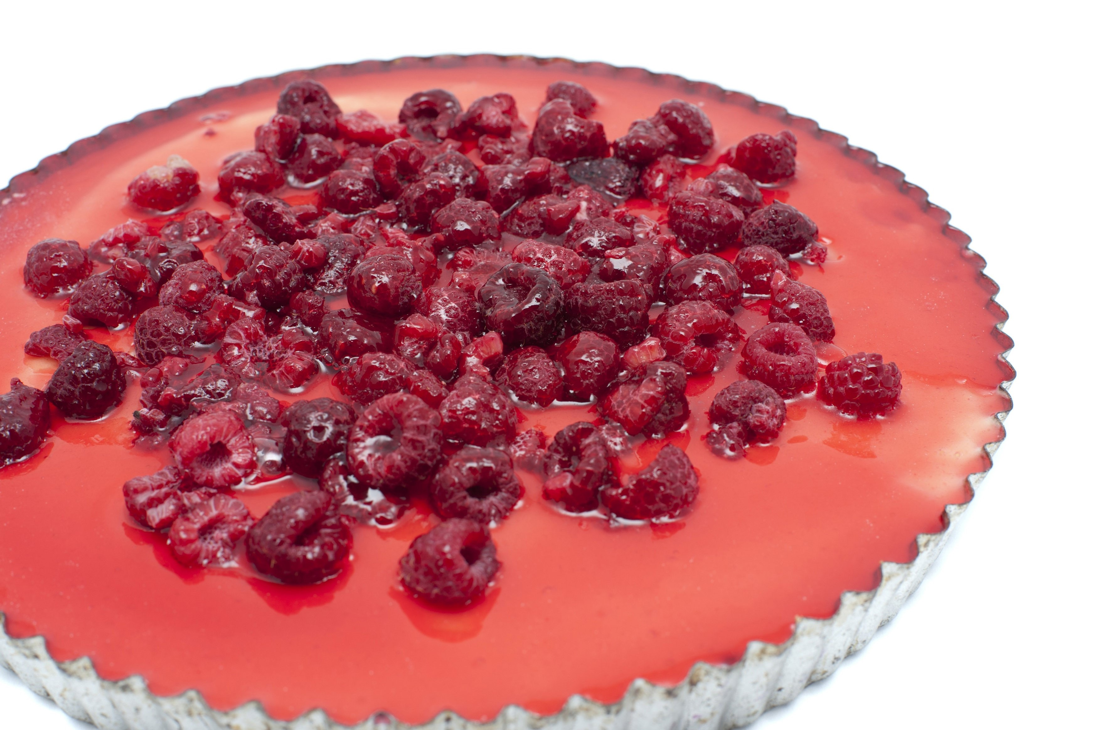 Freshly baked cheesecake in a fluted metal pie pan with a topping of whole fresh raspberries isolated on white