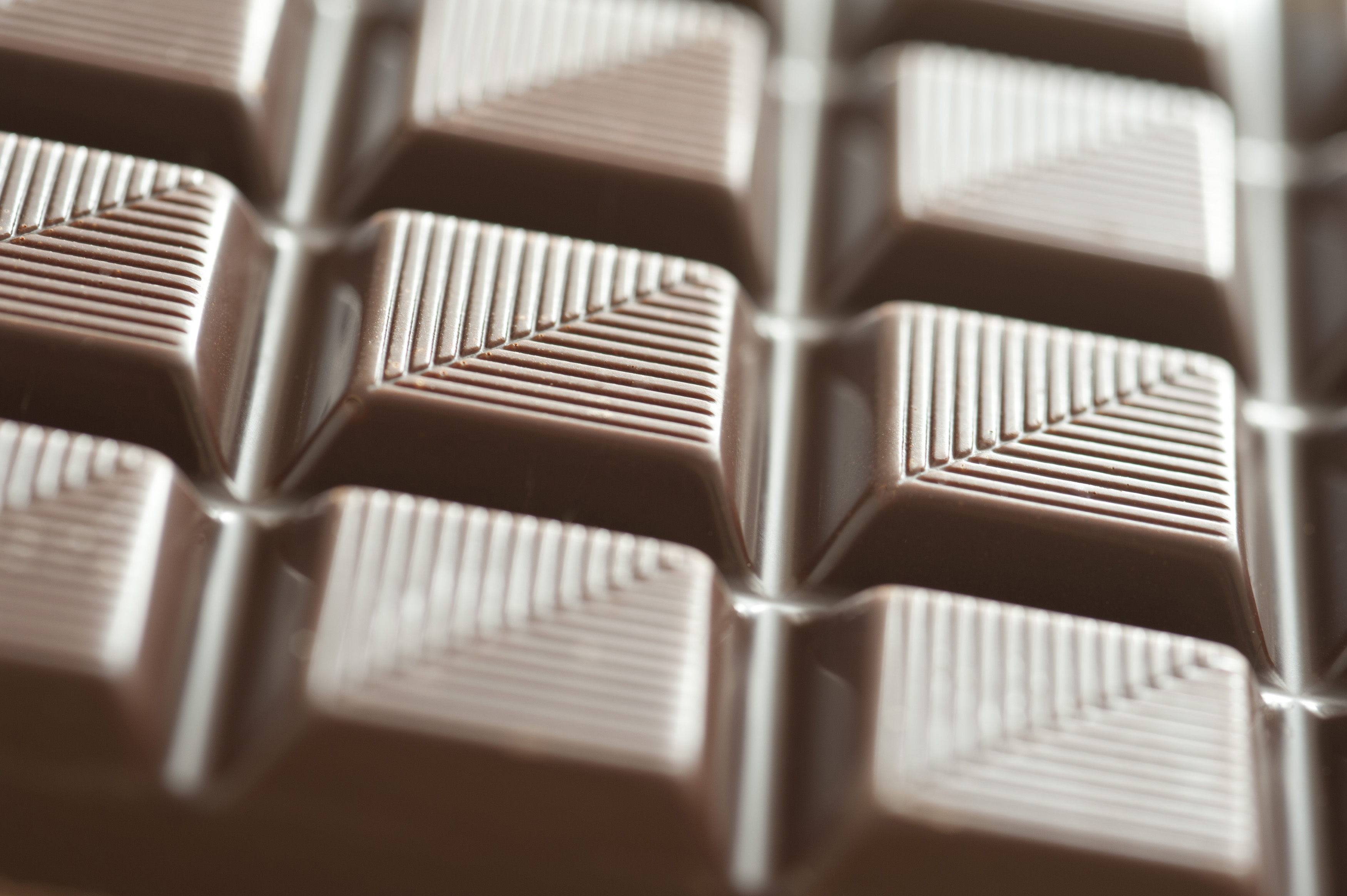 Low angle view of a bar of decorative milk chocolate with a pattern of diagonal lines with shallow DOF