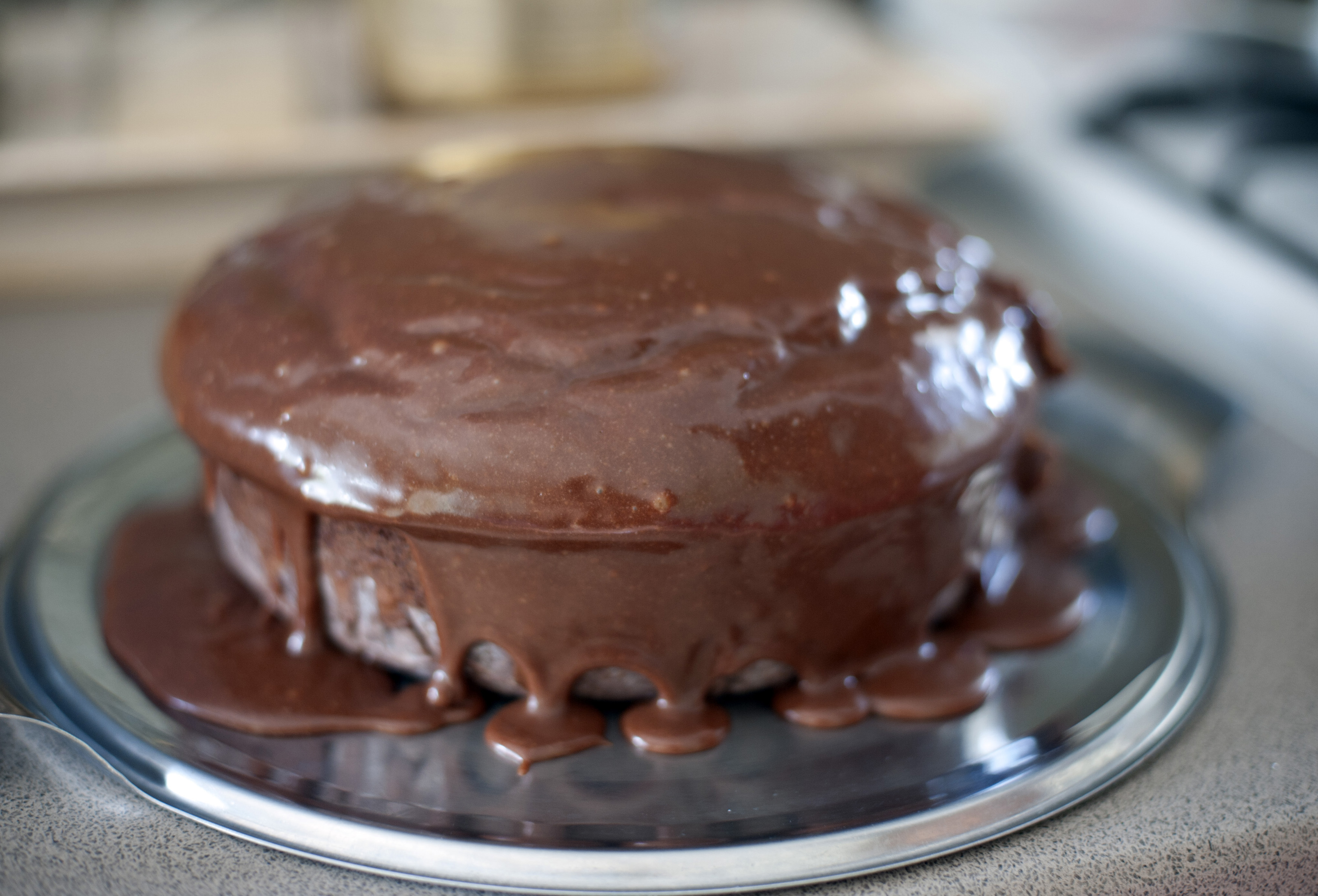 Selective focus close up on round chocolate cake recently coated with icing dripping from the sides on steel pan