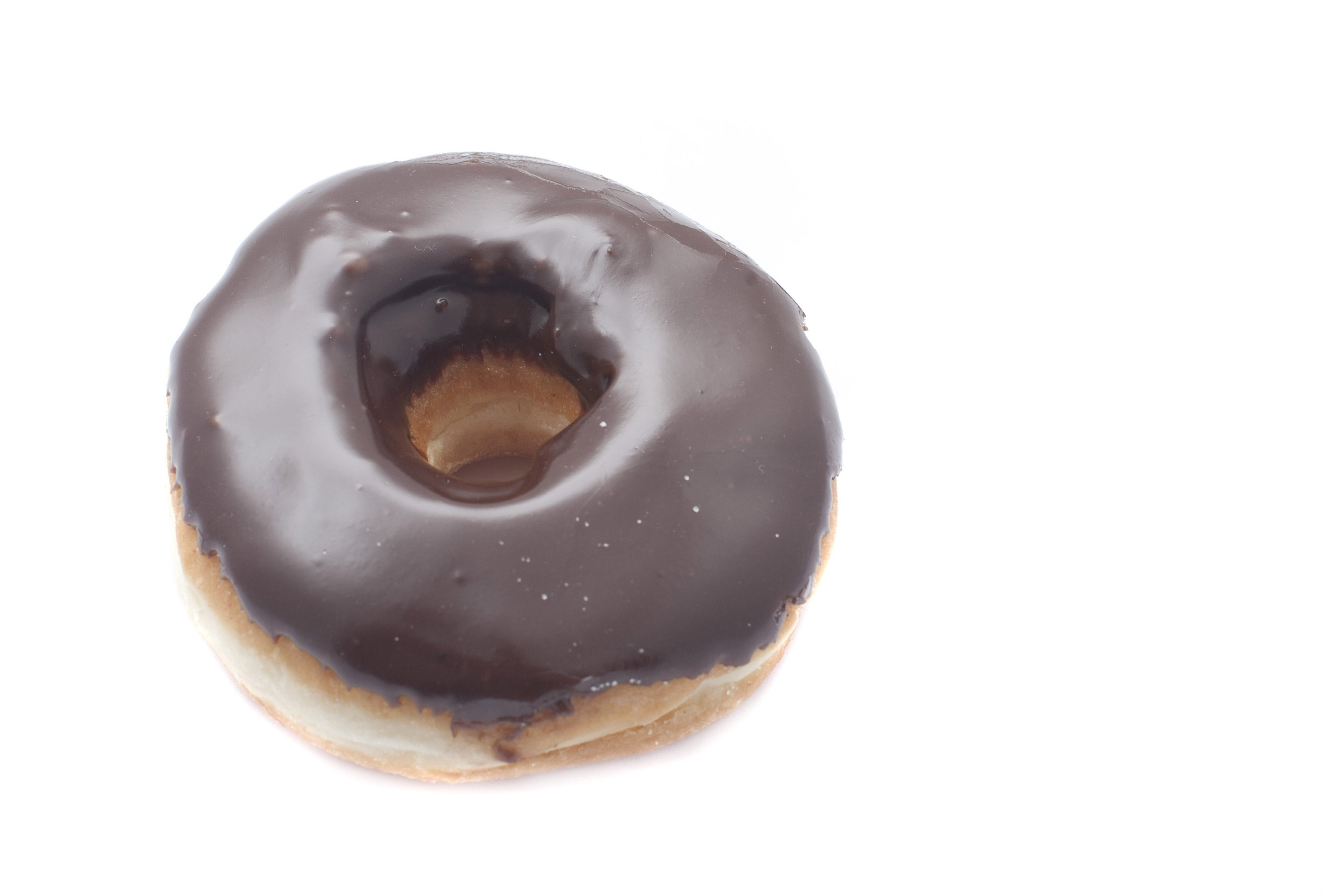 High angle view of a delicious chocolate frosted ring doughnut on a white background